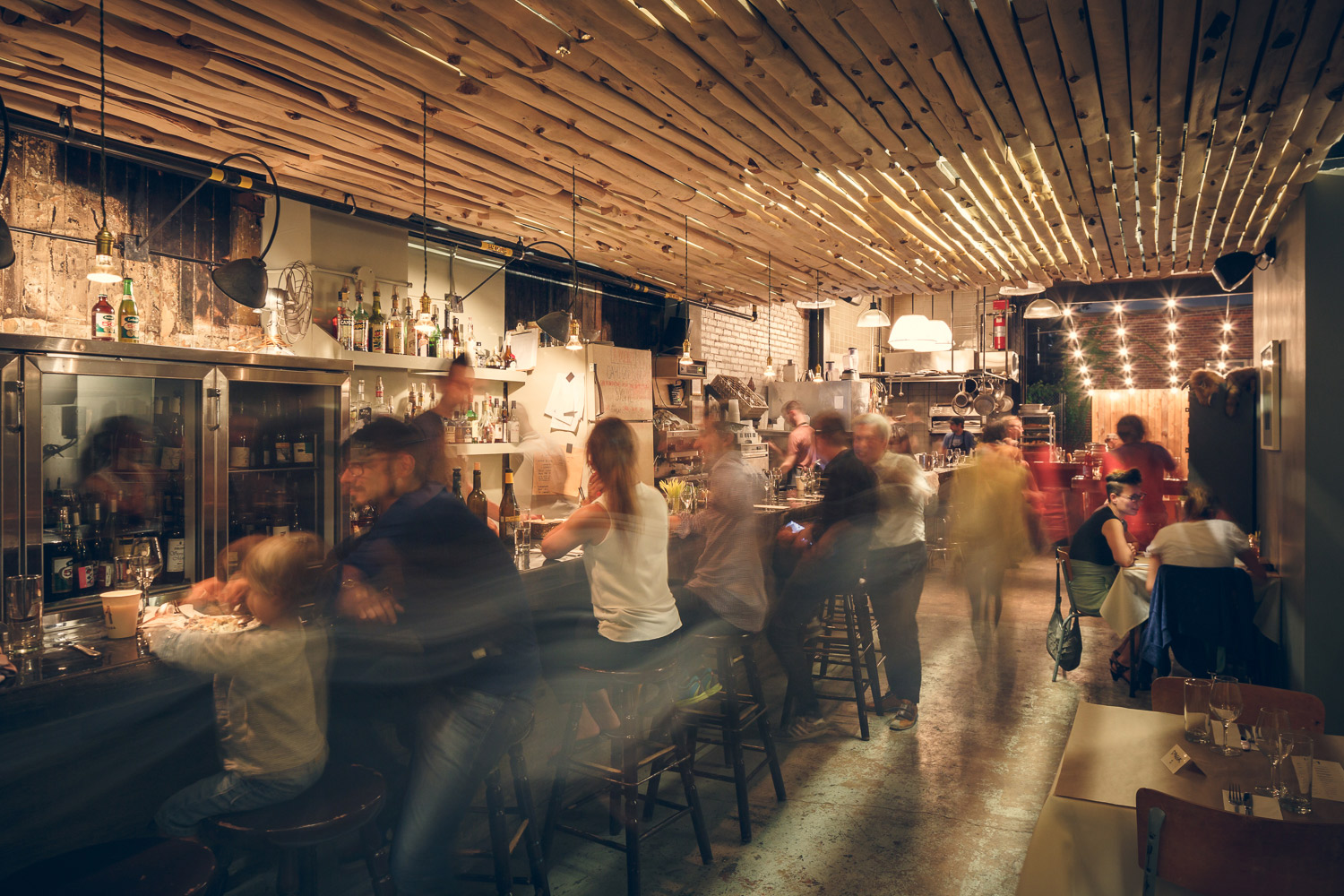 Customers sitting at the bar. The ceiling covered with white cedar without bark shows a shower light. The original walls and concrete floor give an industrial look to the place