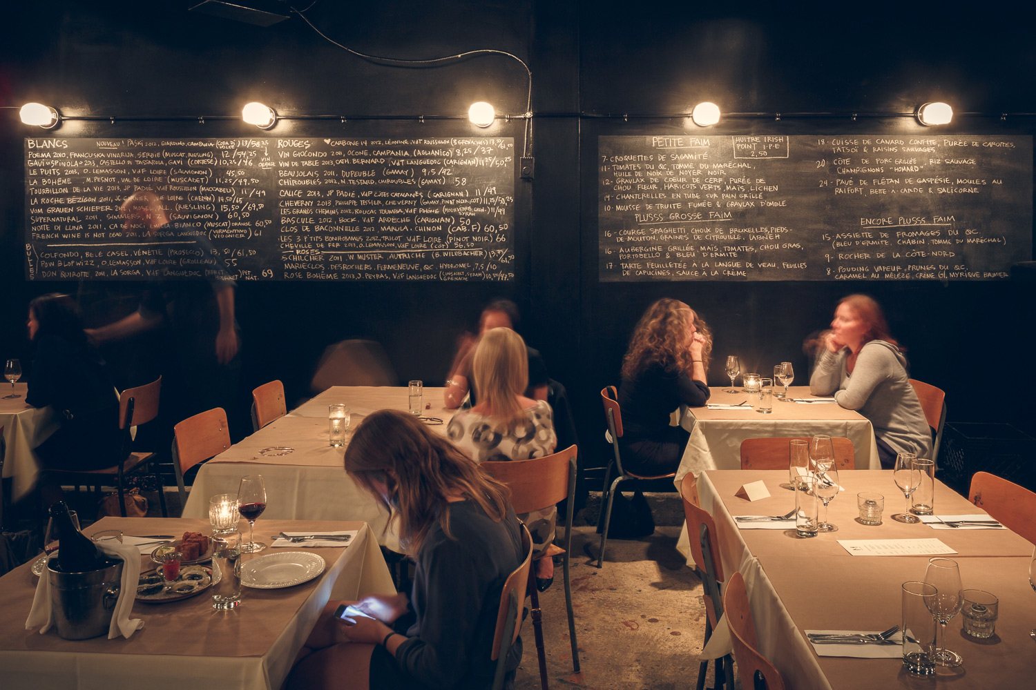 View of the dining room at the Manitoba restaurant. Sober table with white tablecloth and Kraft paper sheet. The back wall painted in black displays two large slate menus with 5 wall lights