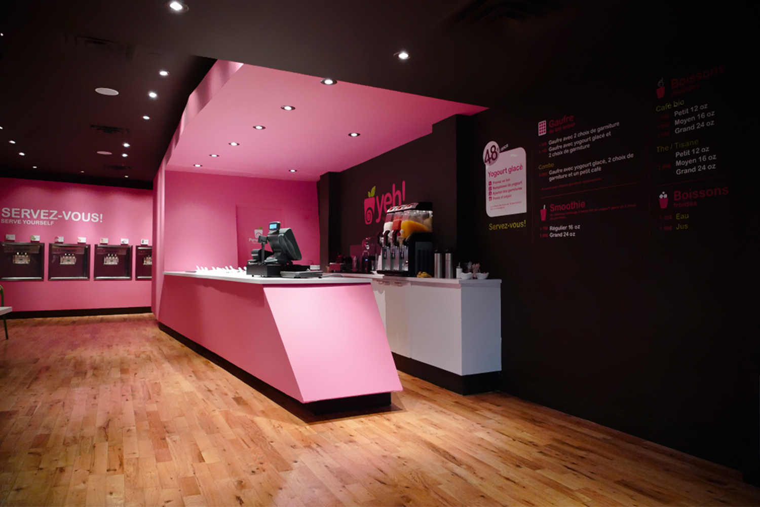 View of the shop with its hardwood floor. The volume of the checkout counter with its angles and its pink color contrasts on the black walls. We see in the distance the built-in vending machines