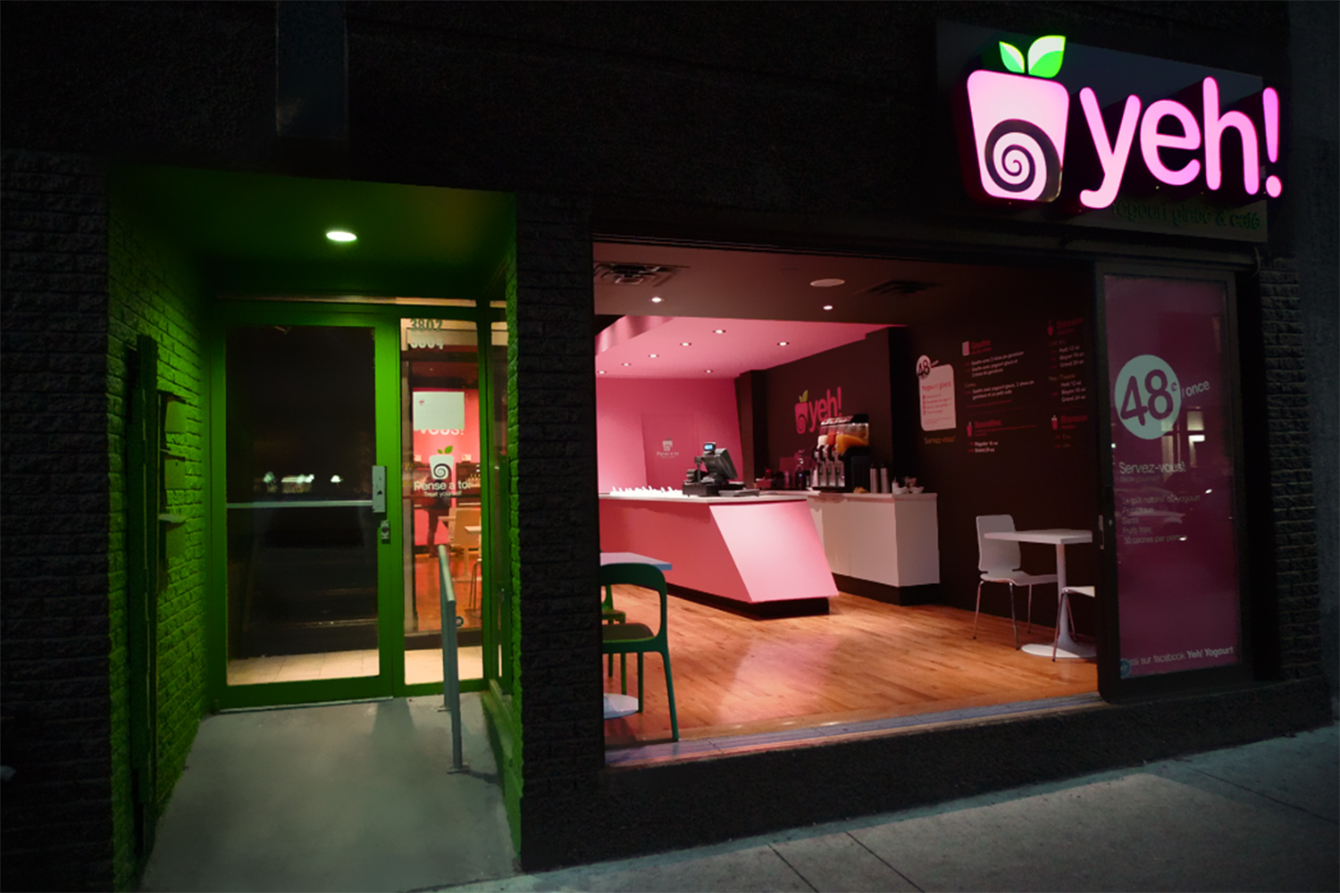 View of the entrance outside the shop on Saint-Laurent Street in Montreal. Brick vault with atypical lighting of green color. The open patio door reveals the interior of the shop