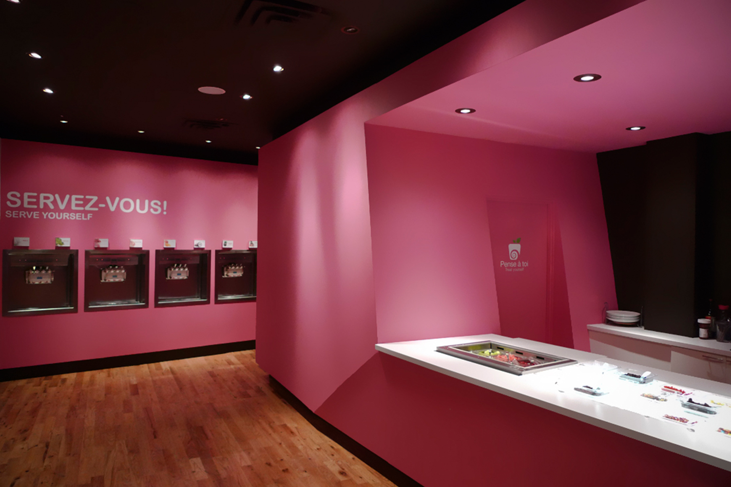 View of the shop with its hardwood floor. The volume of the checkout counter with its angles and its pink color contrasts on a black background. We see in the distance the built-in vending machines
