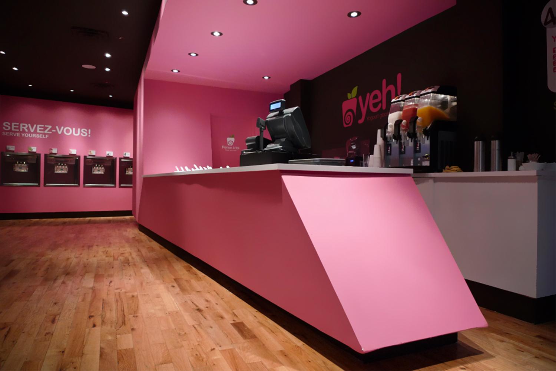 Vue de la boutique avec son plancher de bois franc. Le volume du comptoir caisse avec ses angles et sa couleur rose contraste sur un fond noir. Nous apercevons au loin les distributrices encastrées