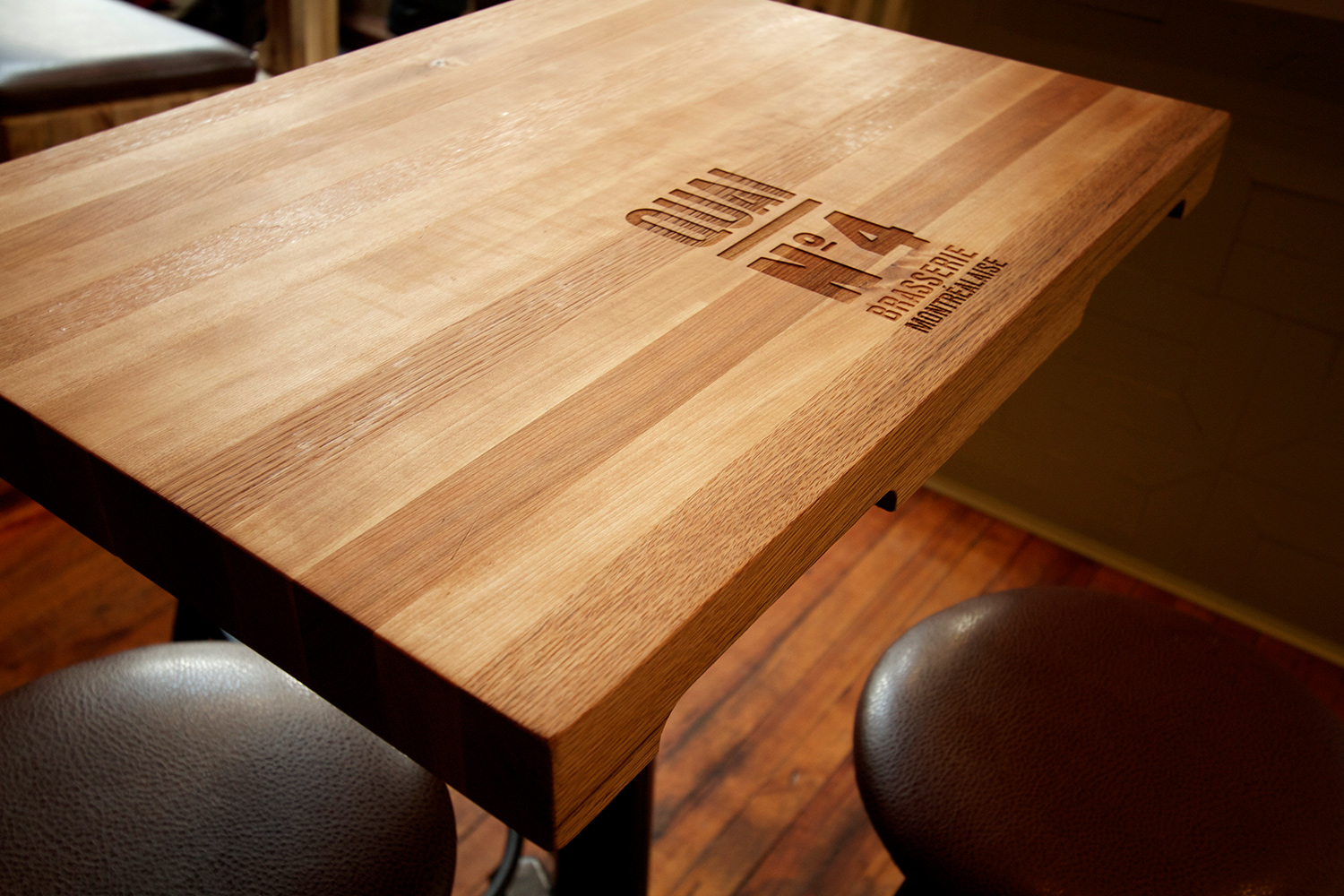 Table composed of 5 different wood species: maple, ash, cherry, beech and oak. Laser engraving of the name of the restaurant and notches on the songs recalling the transport pallets
