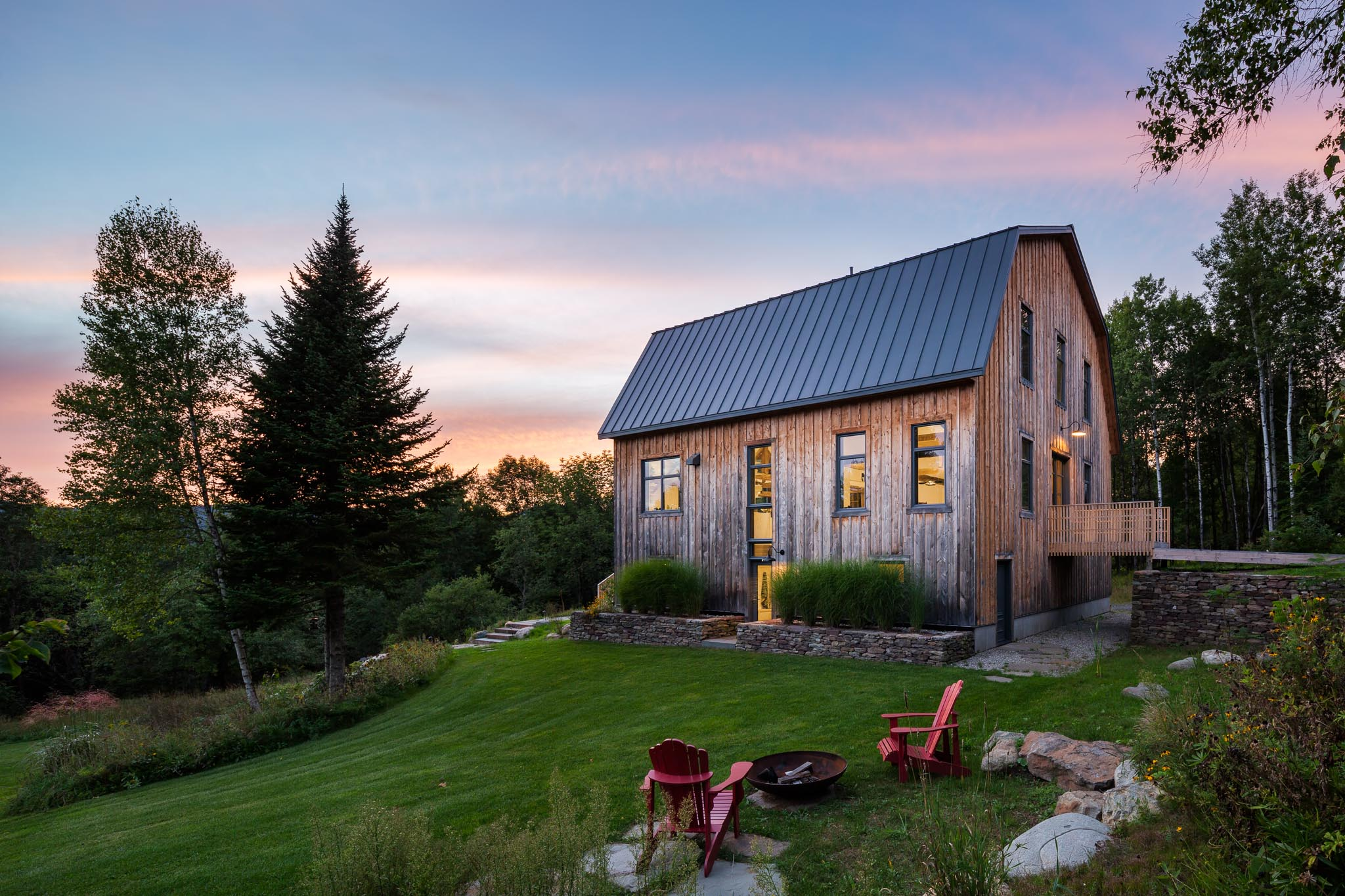 Renovation of a cottage in the Eastern Townships. Footbridge leading to the main entrance. Exterior cladding of boards of cedar boards and batten. Architecture inspired by a barn