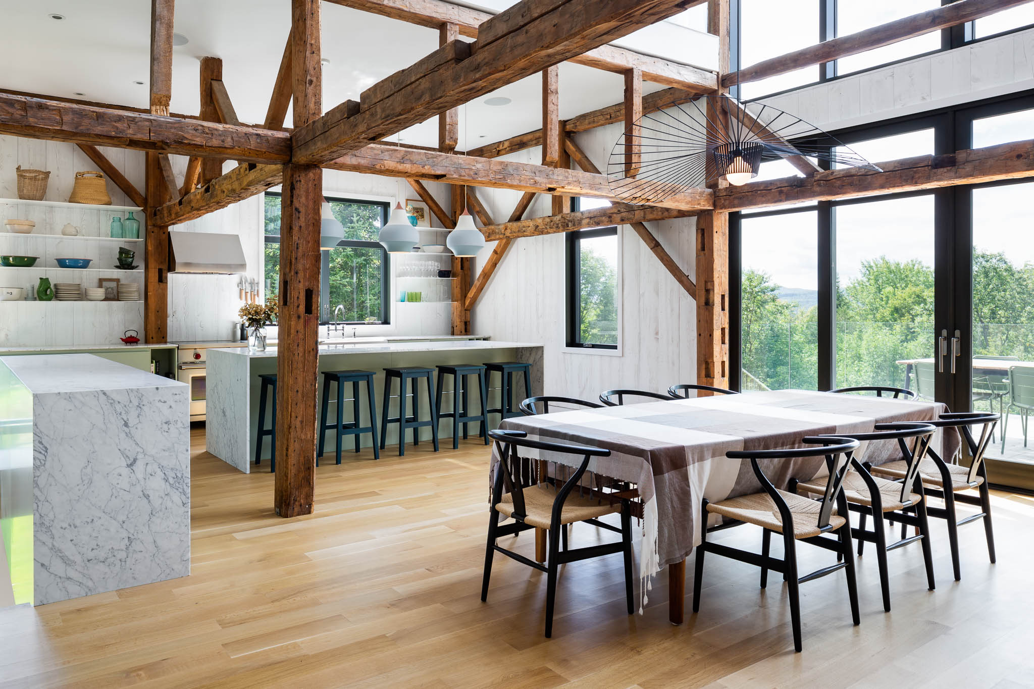 Kitchen with central island, marble counter bianco carrara. Old wooden structure apparent. White painted local hemlock walls and white oak floor. Luminaire Vertigo and Pulsen Circus