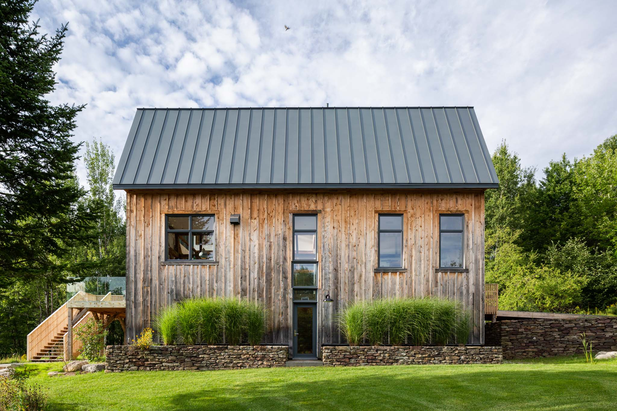 Renovation of a cottage in the Eastern Townships inspired by a barn. Footbridge leading to the main entrance. Exterior cladding of boards of cedar boards and batten. Cedar deck