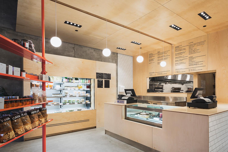 Vue du comptoir caisse fait de contreplaqué merisier avec vitrine pâtisserie. Le mur de la cuisine où est affiché le menu est une continuité en bois du comptoir et de la retombée de plafond.