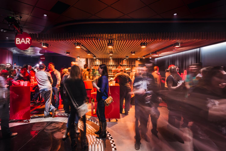 """Bar avec retombée de plafond fait de lattes en noyer noir verticales et luminaires scéniques intégrés. Cercle signalétique rouge avec """"BAR"""" en points lumineux. Mobilier rouge et clients en mouvement"""