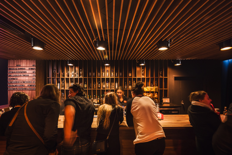 Bar et retombée de plafond faite de lattes en noyer noir verticales et luminaires scéniques récupérés. Menu bar en noyer avec lettres individuelles découpées au laser noir et blanc.