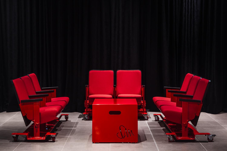 Mobilier de salle de spectacle récupérés. Sièges vintages soudés sur piètement avec roulettes finis rouge lustré. Table empilable en pliage d'acier avec découpe laser du logo et poignées intégrés