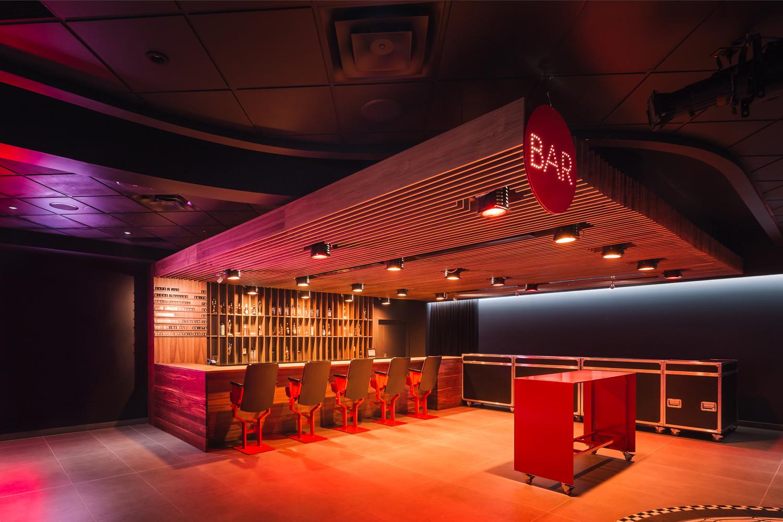 Bar fabriqué en noyer noir et luminaires scéniques récupérés. Tabouret de bar sur mesure fabriqué avec d'anciens sièges de salle de spectacle récupérés. Caissons transformés en bars mobiles
