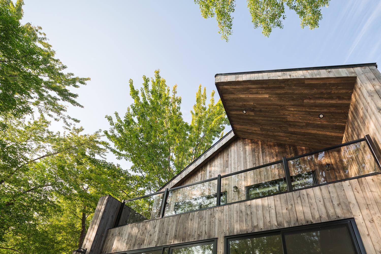 Maison secondaire avec balcon dans la chambre principale. Revêtement extérieur en bois ( pruche grise ) planches verticales. Toiture à 2 pentes
