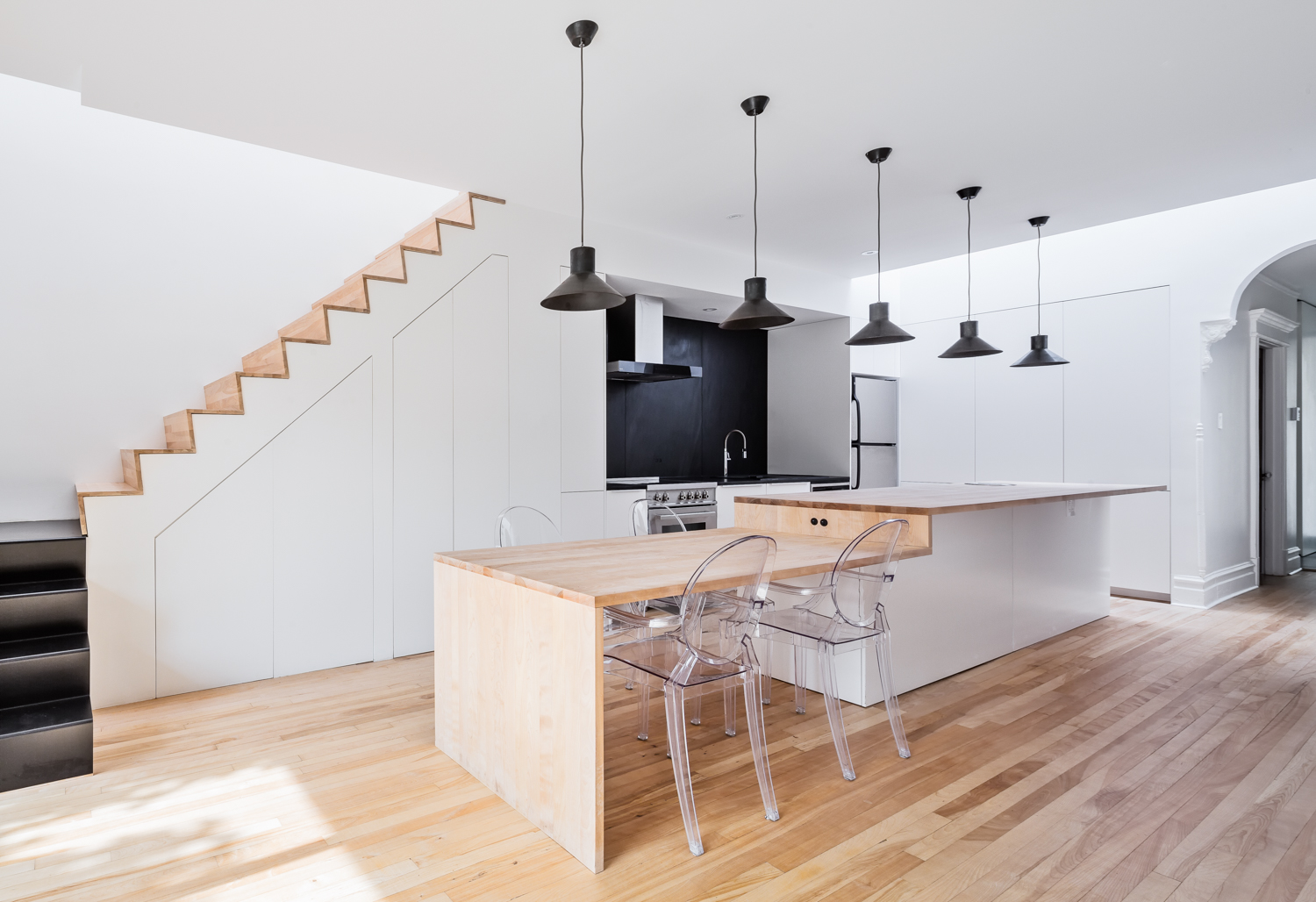 Renovation of the kitchen. Table and island in continuity. Backrest and counter in black slate from Quebec. Storage under the stairs. New skylights, arches and existing details preserved