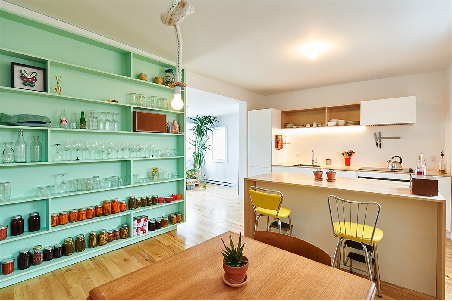 Renovation of a duplex. Kitchen layout. Prefabricated cabinets and custom wood counters. Turquoise integrated bookcase