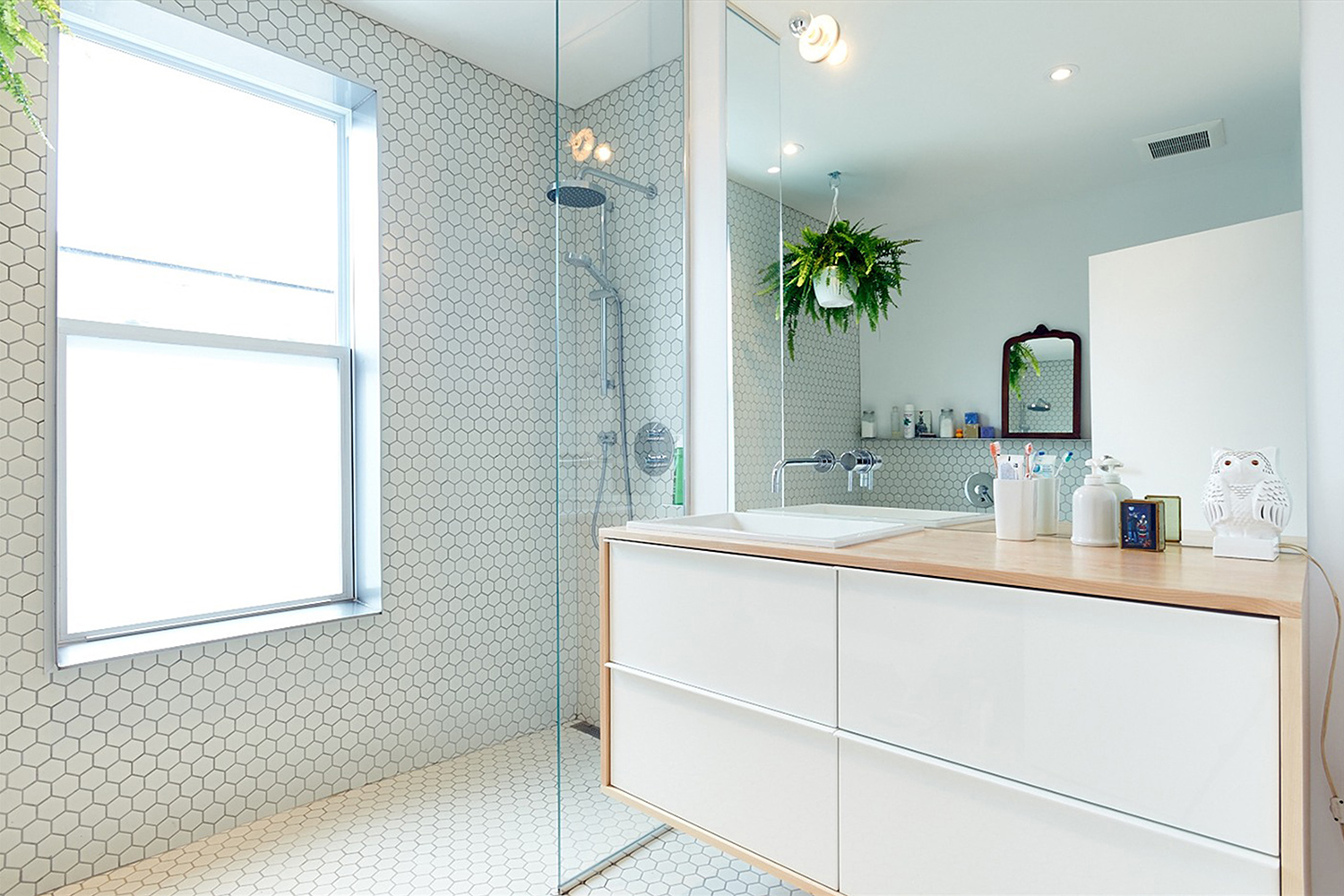 Renovation of bathroom. Floor and octagonal white mosaic wall. Full height custom mirror with white vanity cabinet. The cherry wood counter surrounds the furniture hanging on the wall
