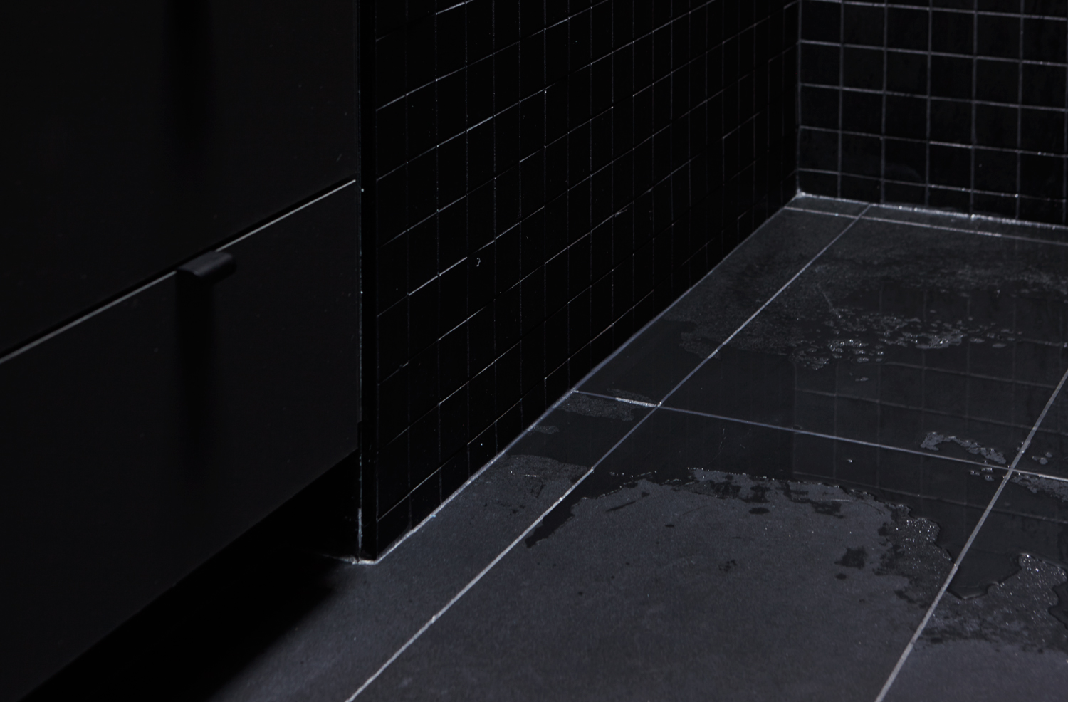 View of the corner of the bathroom. Black ceramic floor with black 2x2 mosaic on the wall. Black washbasin cabinet.