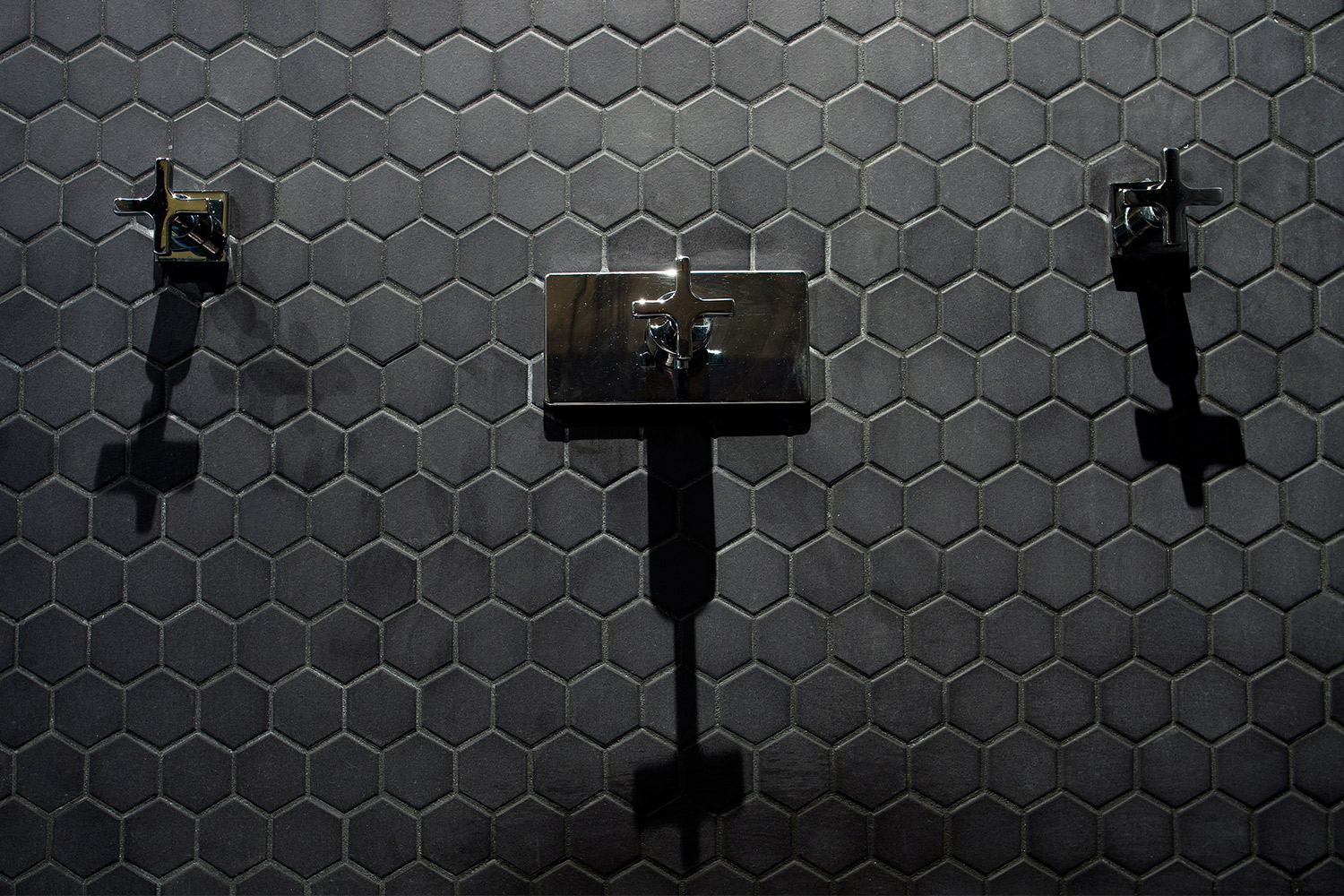 Renovation of monochrome bathroom in an apartment. Detail view of the shower faucet on black hexagonal mosaic wall.
