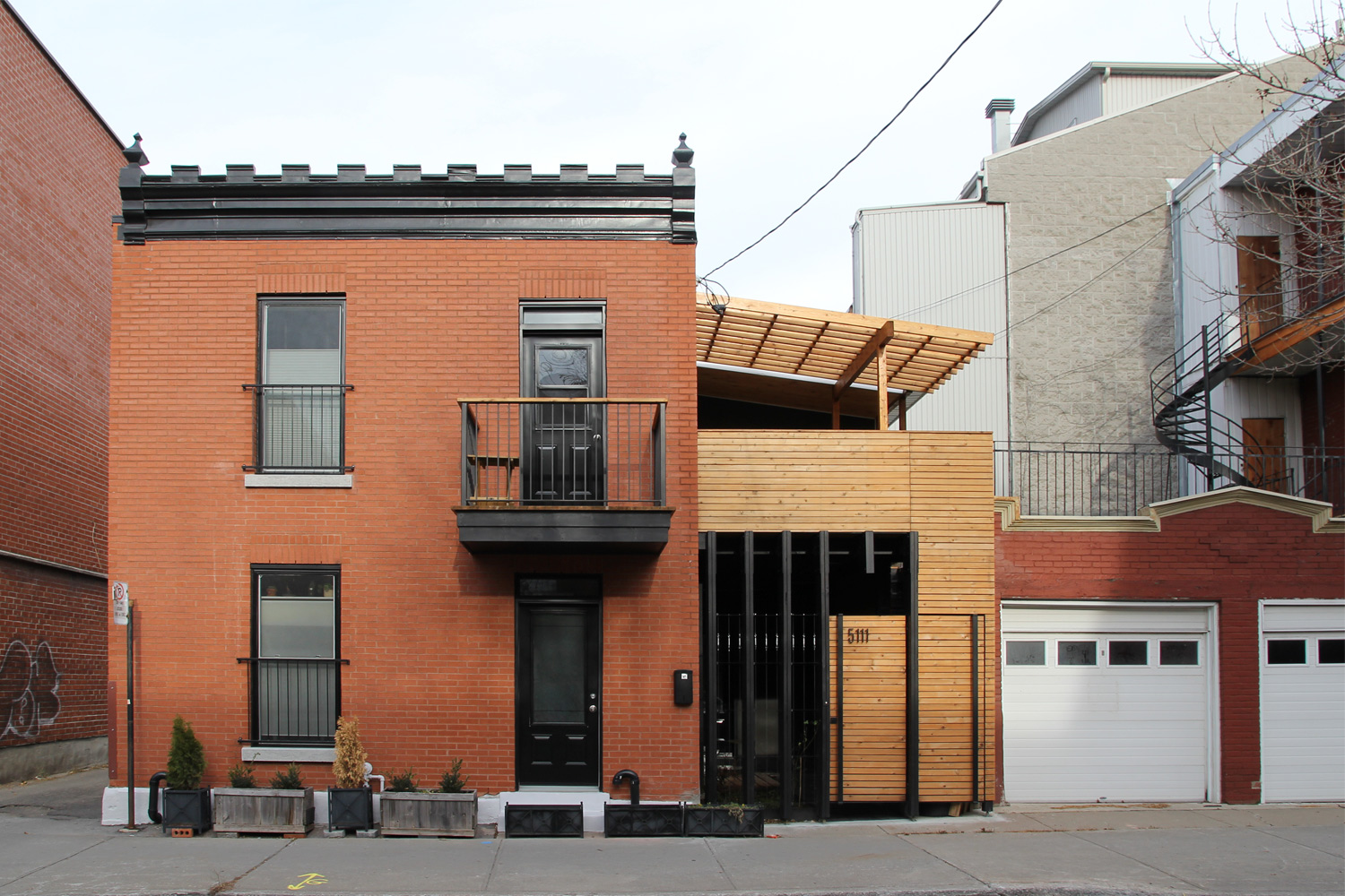 Privacy fence on the Plateau Mont-Royal. Made of natural wood and black wood. Pergola on the floor.
