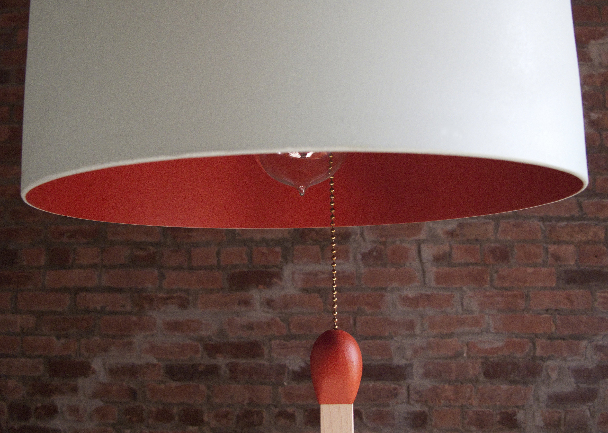 Lamp made from a gas tank. A match in giant format is suspended in the center. Exterior painted blue gray and interior finished red ocher.