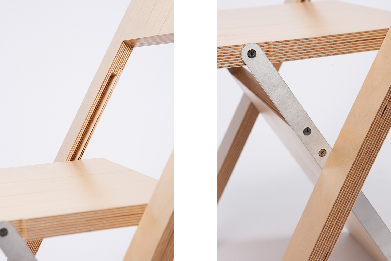 Détail de la chaise pliante en merisier russe et acier inoxydable. Elle ne fait qu'un pouce une fois repliée.