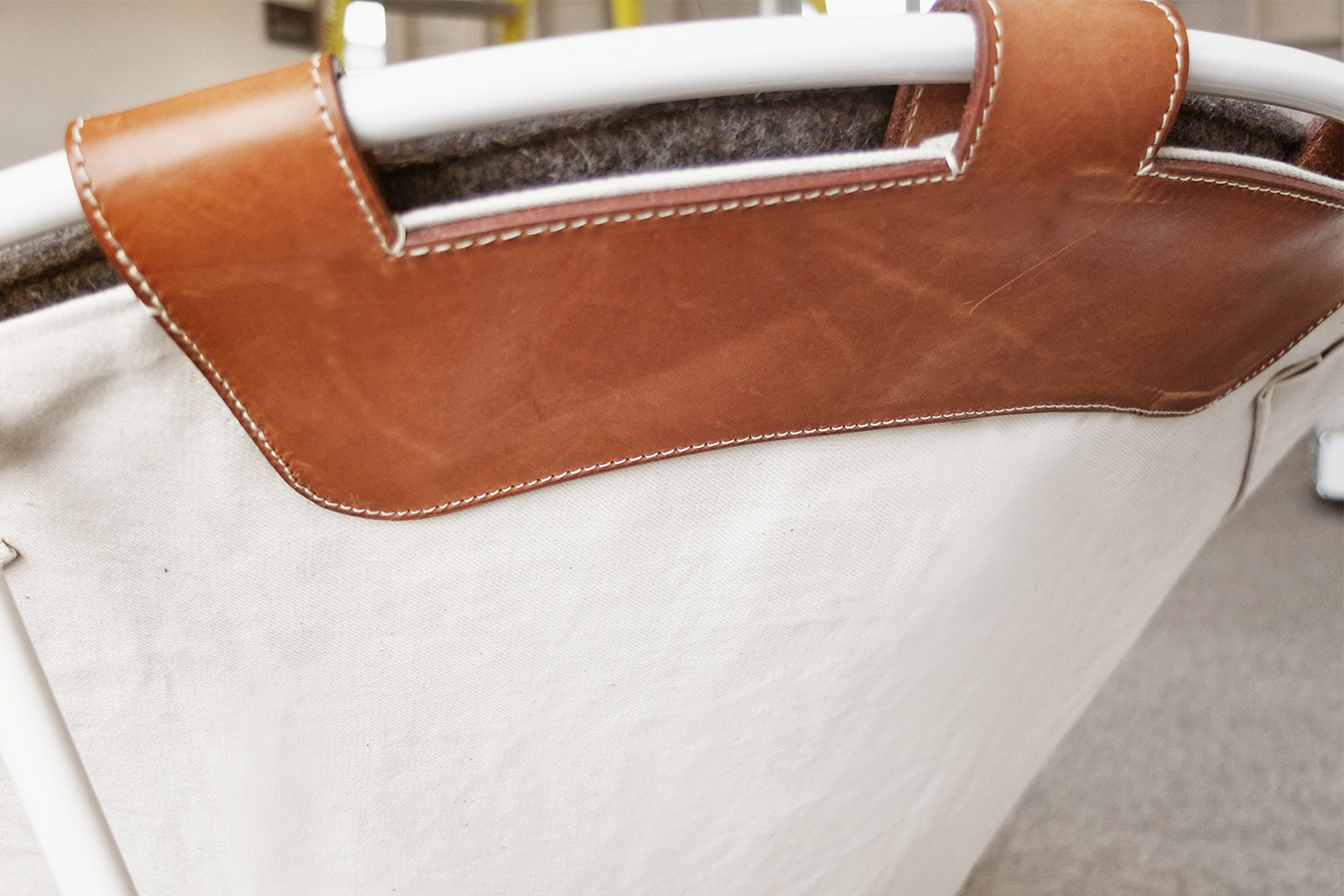 Detail of a chair made to measure for the hotel La ferme. Felt cover with white canvas and brown leather reinforcement. Metal structure in white stem