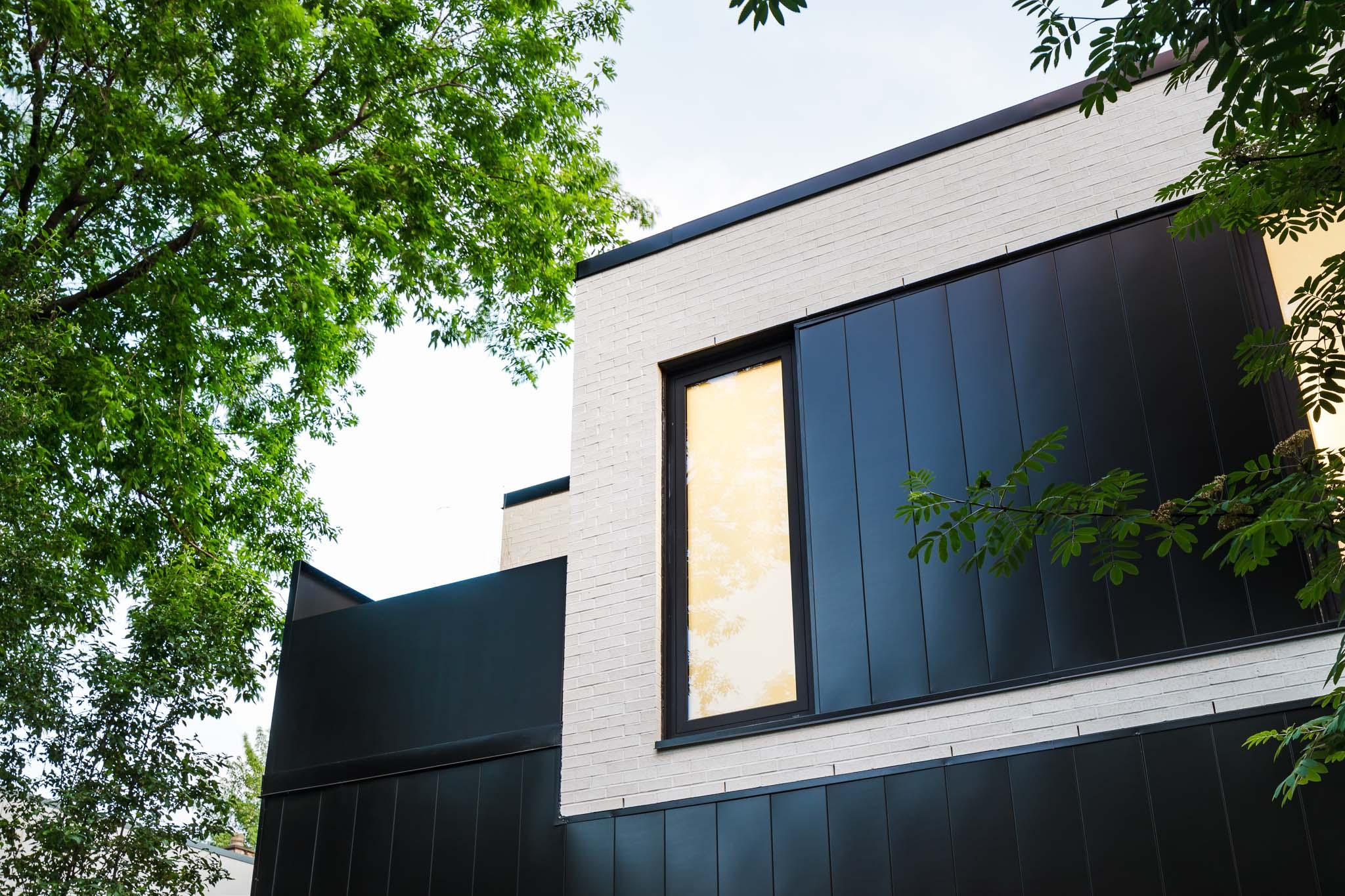 Ancien atelier transformé en duplex. Grande aire ouverte. Luminaire bleu de Simon Johns. Poutres apparentes. Plancher de béton poli. Porte de garage dans le salon.
