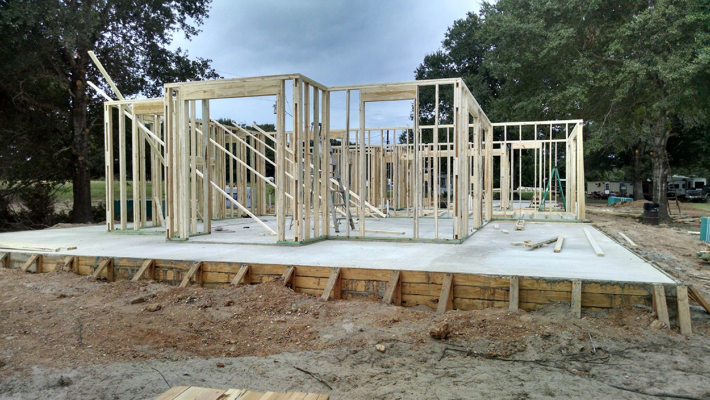 Framing started. Notice the building and trailer in the right back- that's where we lived during construction