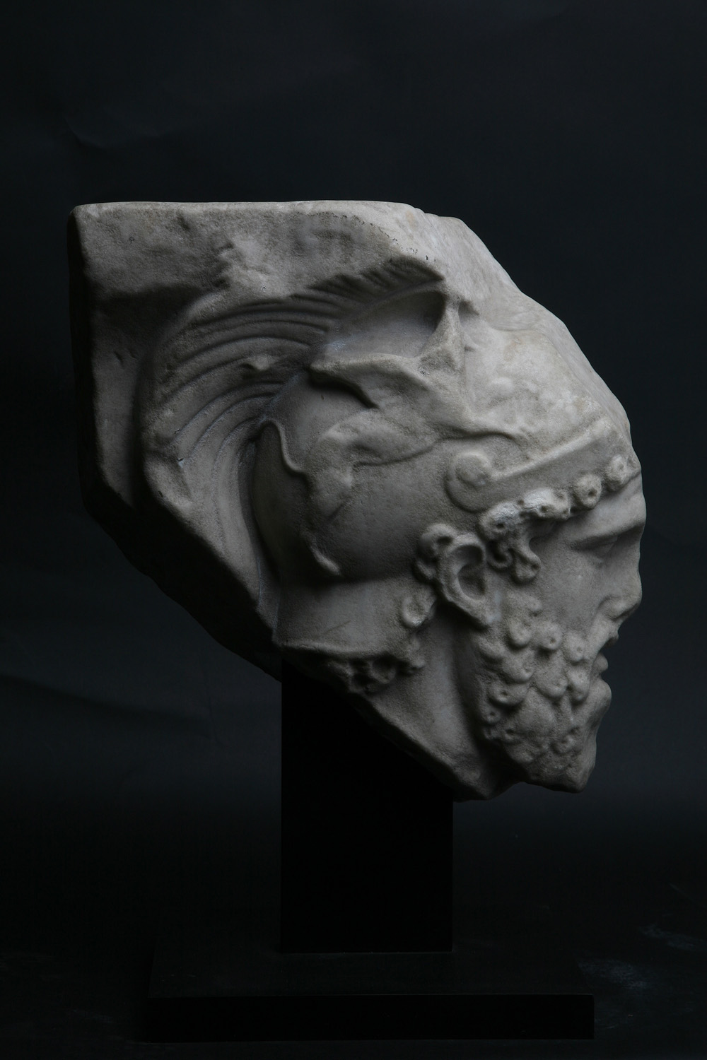 Roman marble relief fragment depicting the head of Mars ,Circa 2nd century AD,Height 29 cm,Courtesy of Rupert Wace Ancient Art Ltd, London