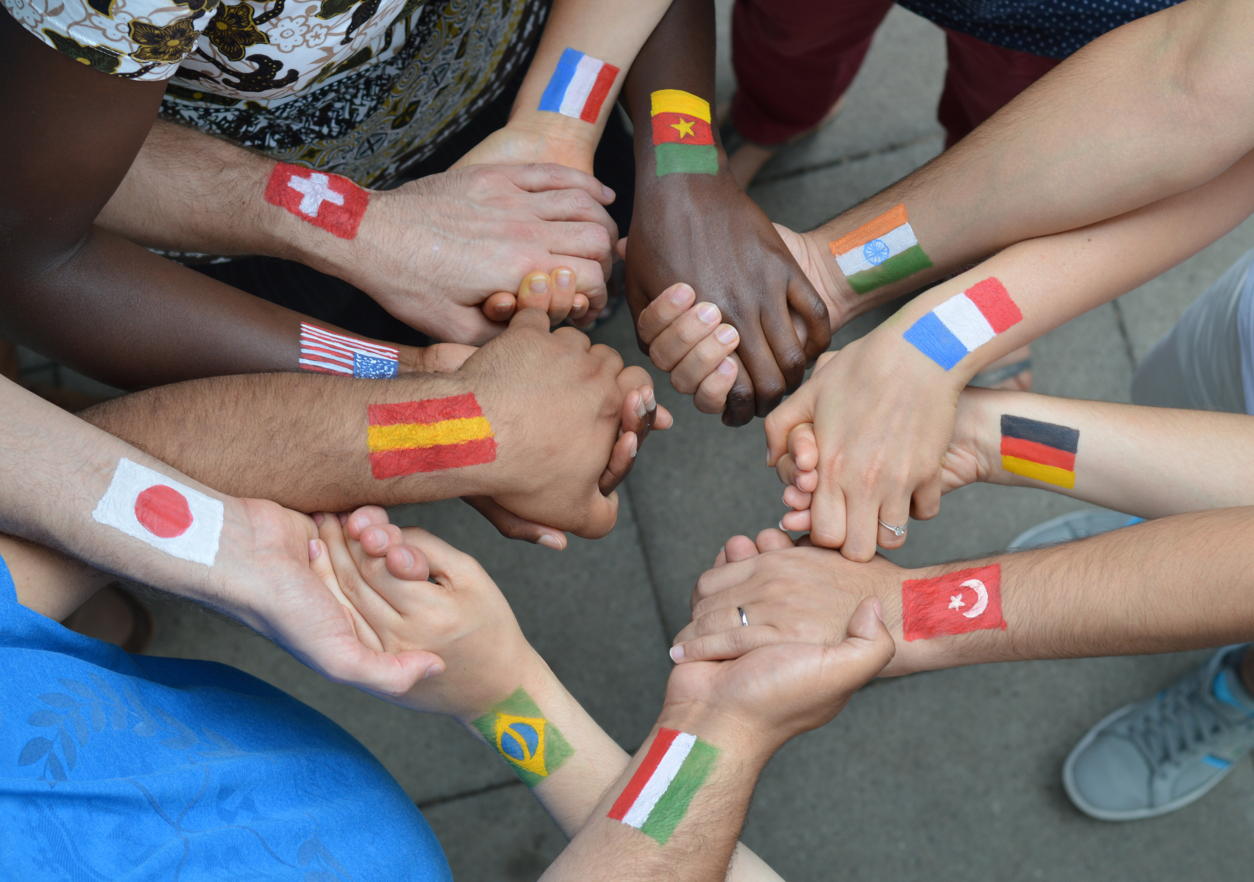 six people holding hands showing flags of 12 nations in global partnerrship