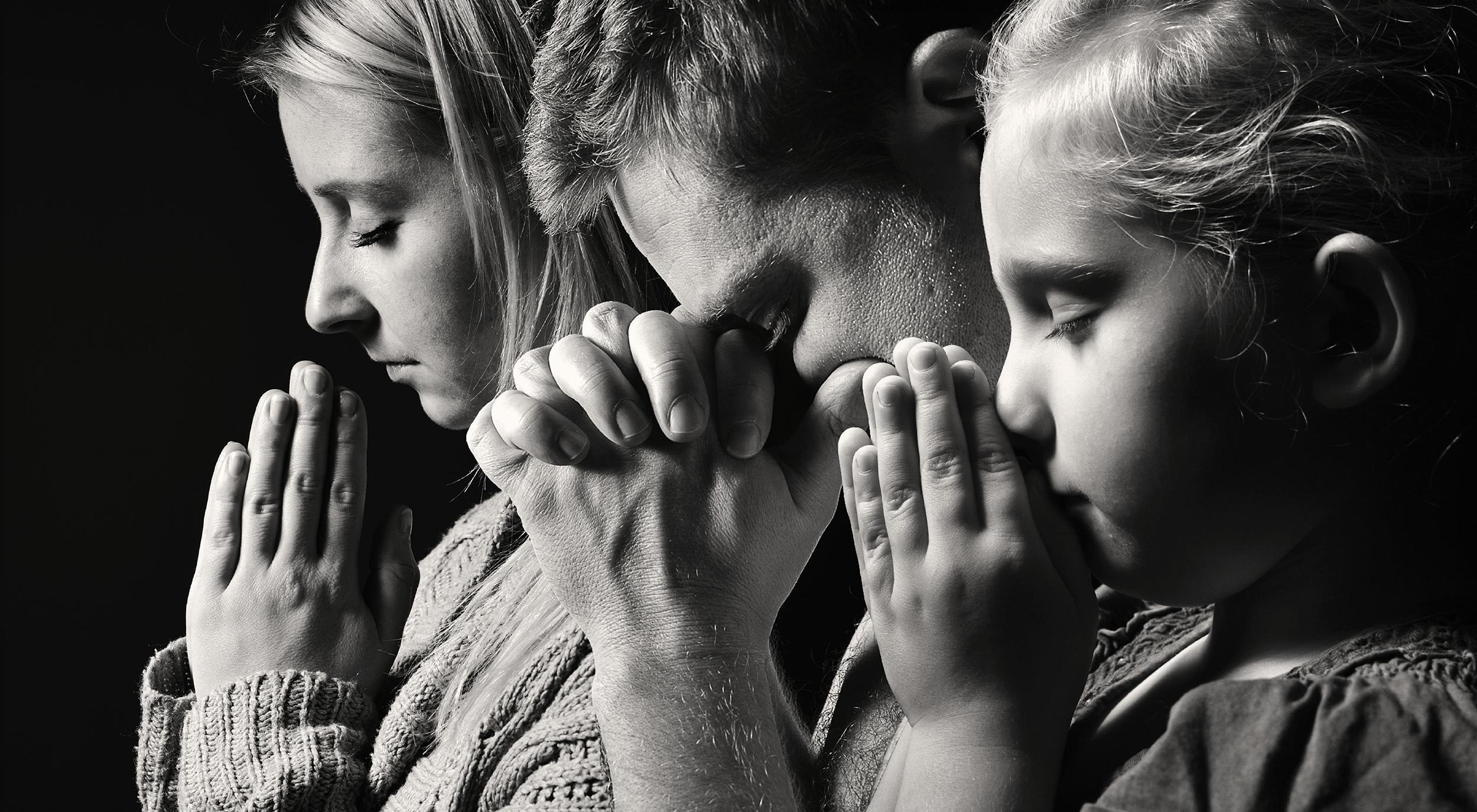 Mom, dad and daughter worshiping