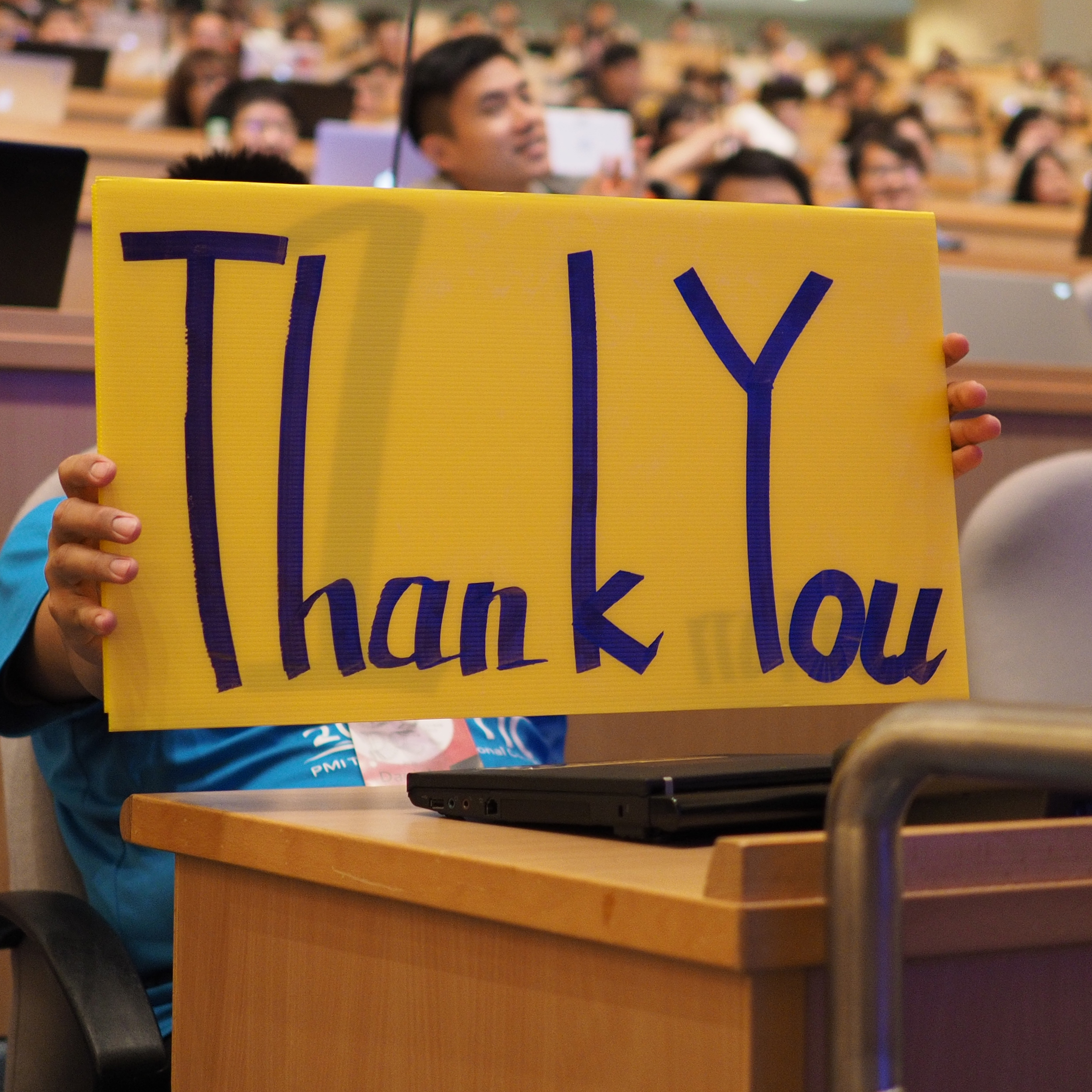 Image of students saying thank you and holding a sign.