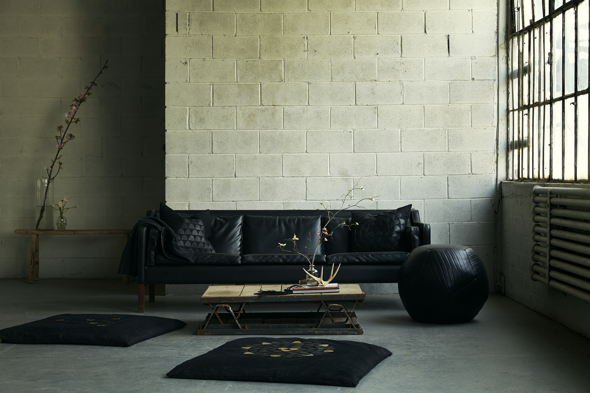 Emblem Pyramid Floor Cushion  in Black Denim with Mixed Metallic leather appliqué,  Emblem Mandala Floor Cushion  in Black Denim with Mixed Metallic leather appliqué,  Large Pyramid Emblem Pillow  in Black Denim with Black leather appliqué ,  Large Mandala Emblem Pillow  in Black Denim with Black leather appliqué,  King Banded Ottoman  in Black and  Whiplash Tassel Bag Accessory  in Black (available upon special request) : Nicole Watts Studio - Brooklyn Loft | Photo: Pär Olofsson
