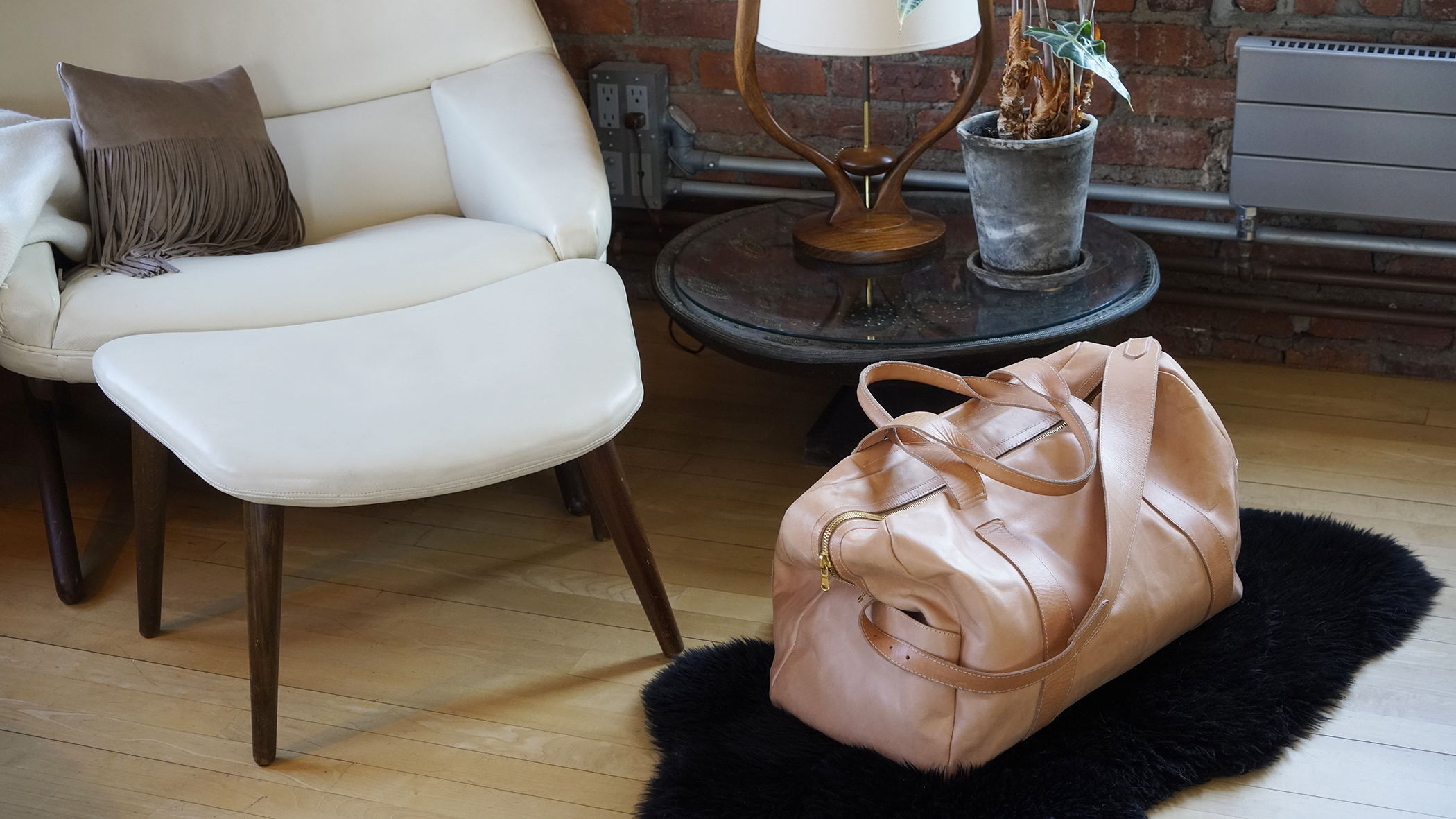Range Travel Bag  in Veg Tan and  Fringe Pillow  in Taupe | Photo: Gerald Forster