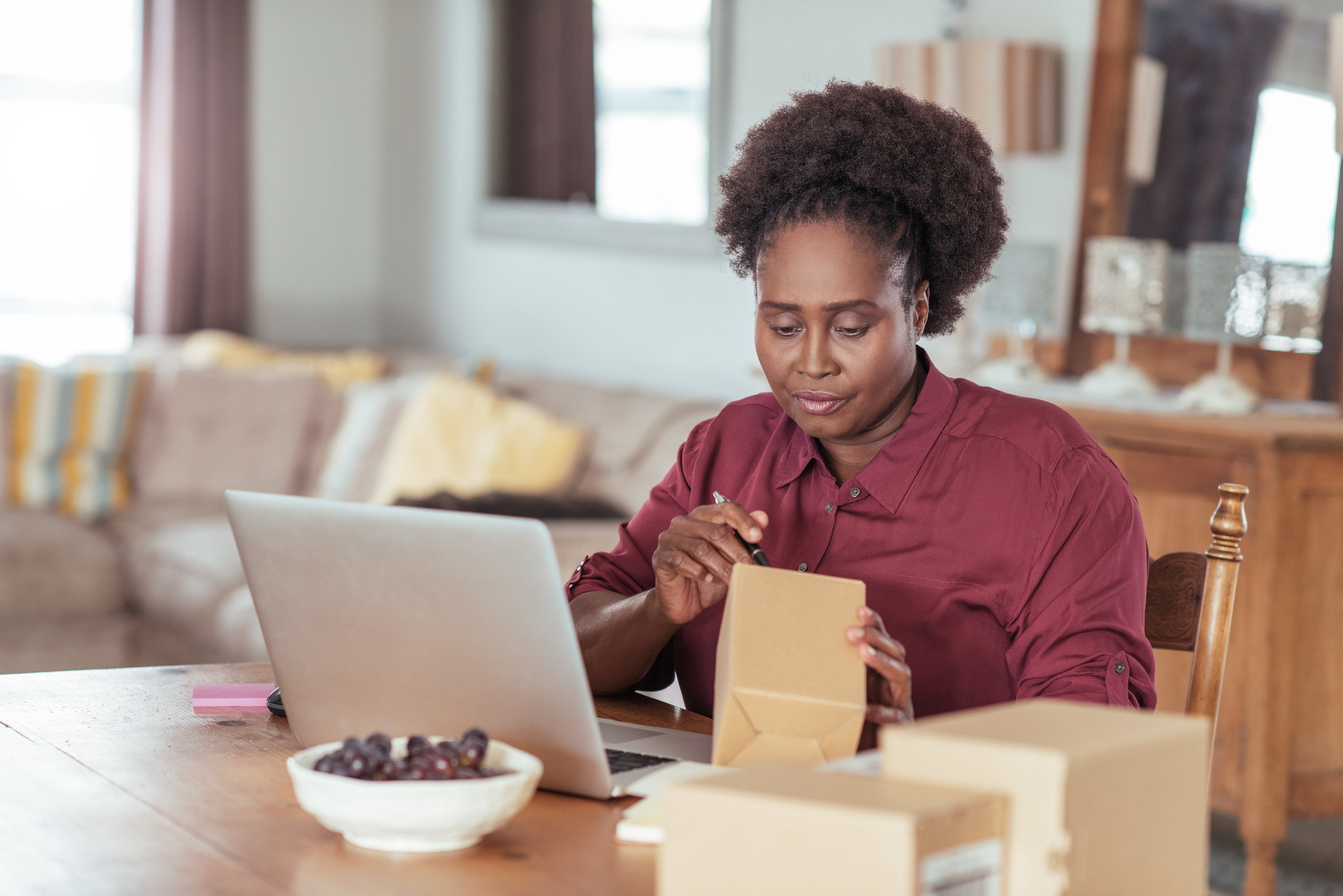 Copy of Young African woman labeling packages while working from home
