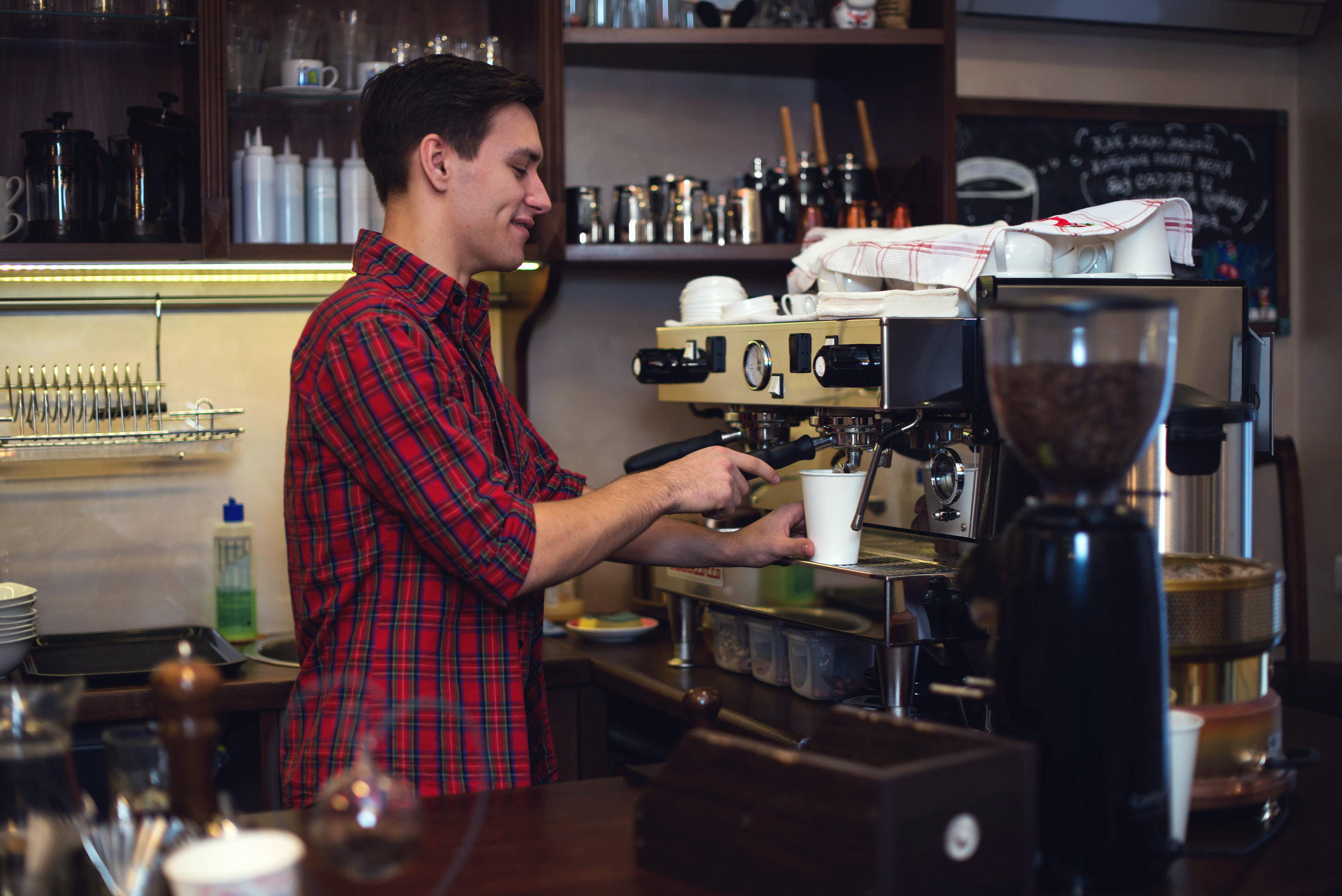 Young handsome barista hipster making coffee for his clients in