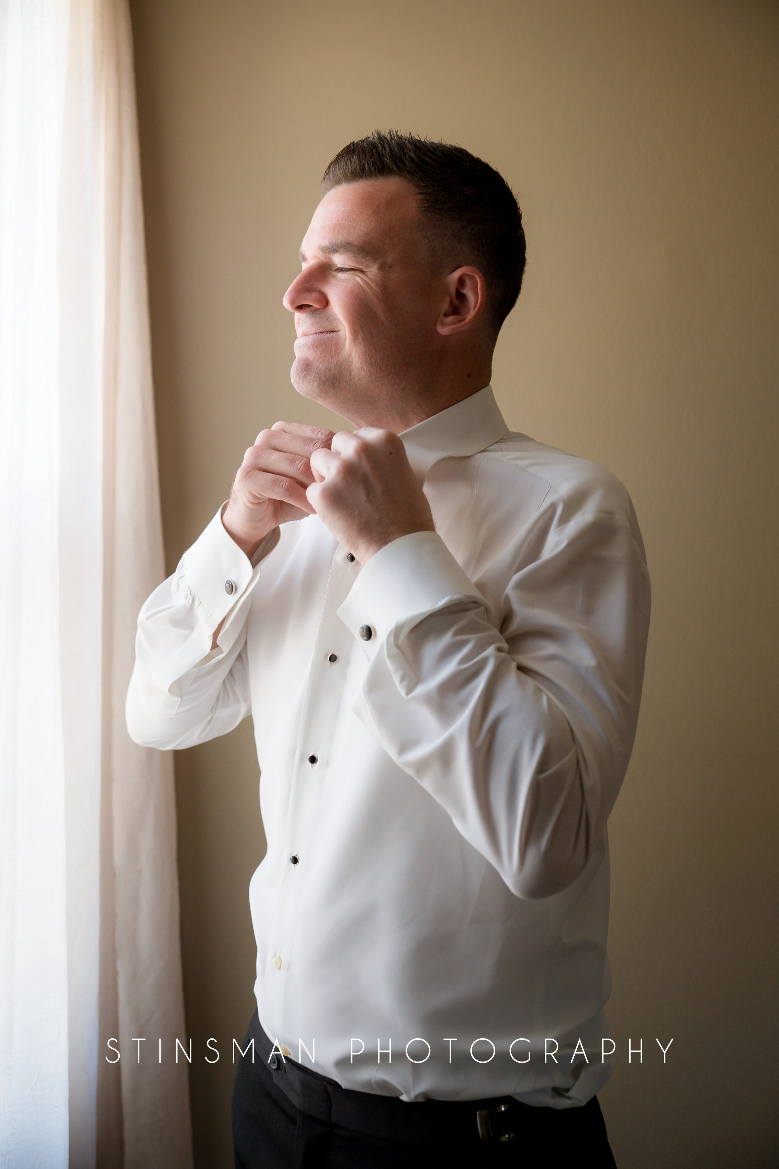 groom getting dressed for his wedding day wearing a white bow tie