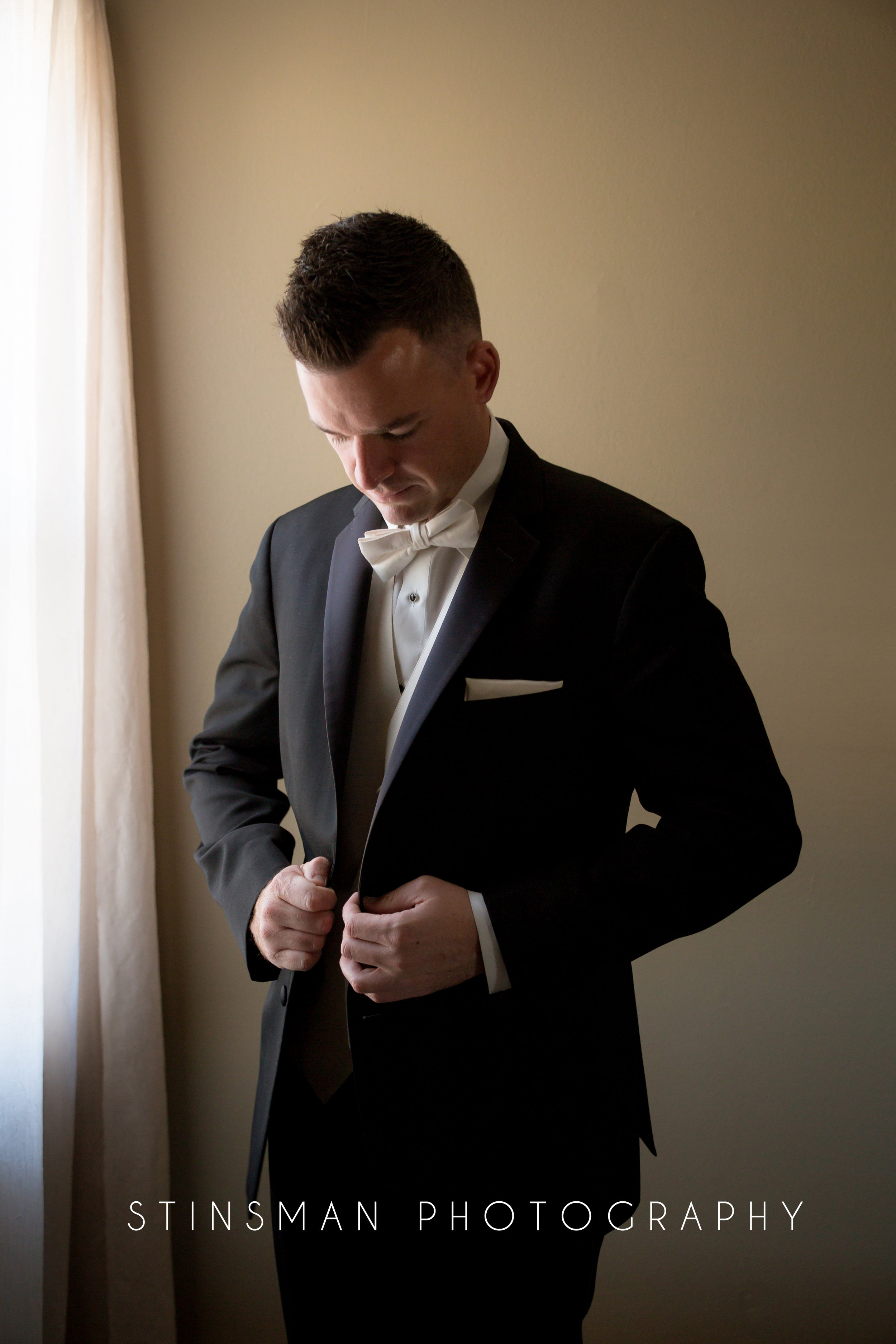 groom putting on his jacket for wedding photos