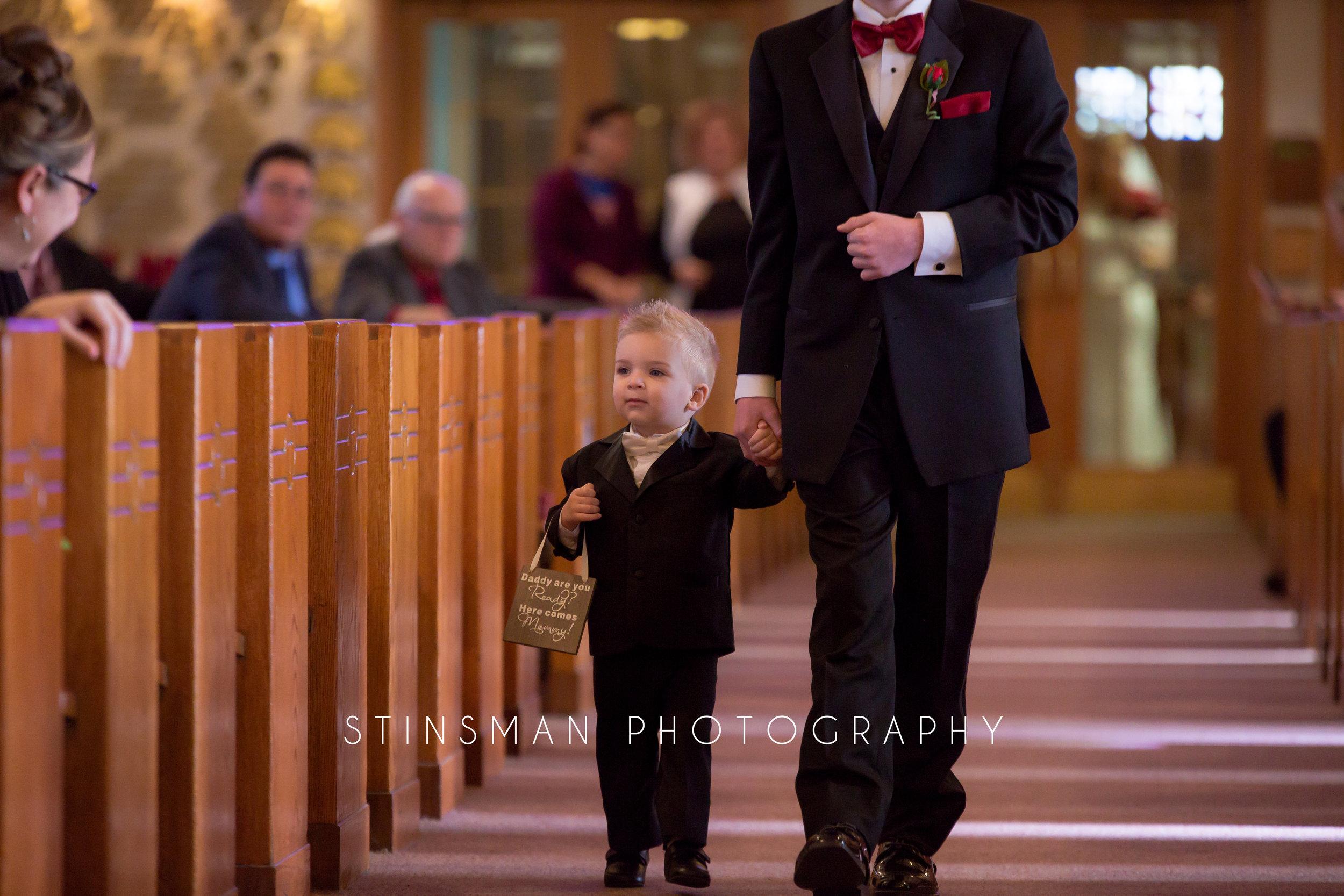 son walking down the aisle at the church