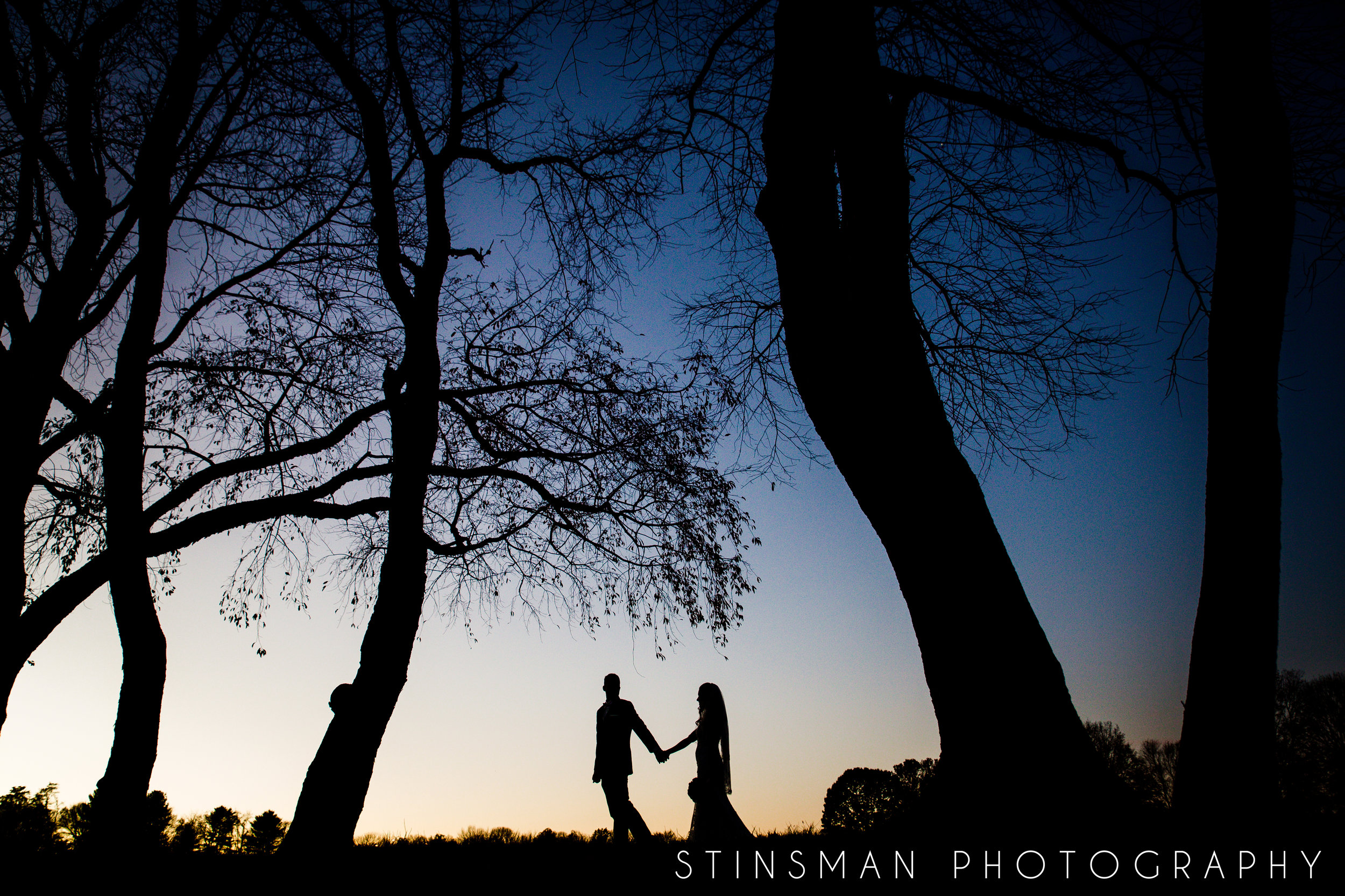 shiloette photo of a bride and groom kissing and walking
