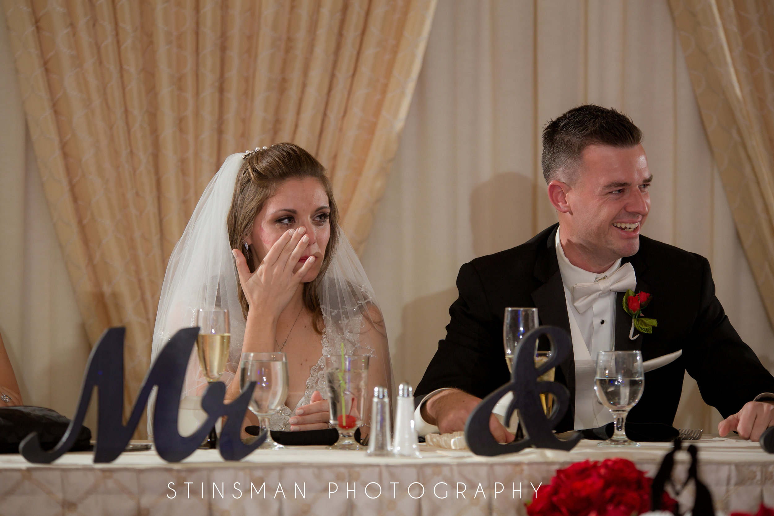 bride wiping away a tear during the matron of honor speech
