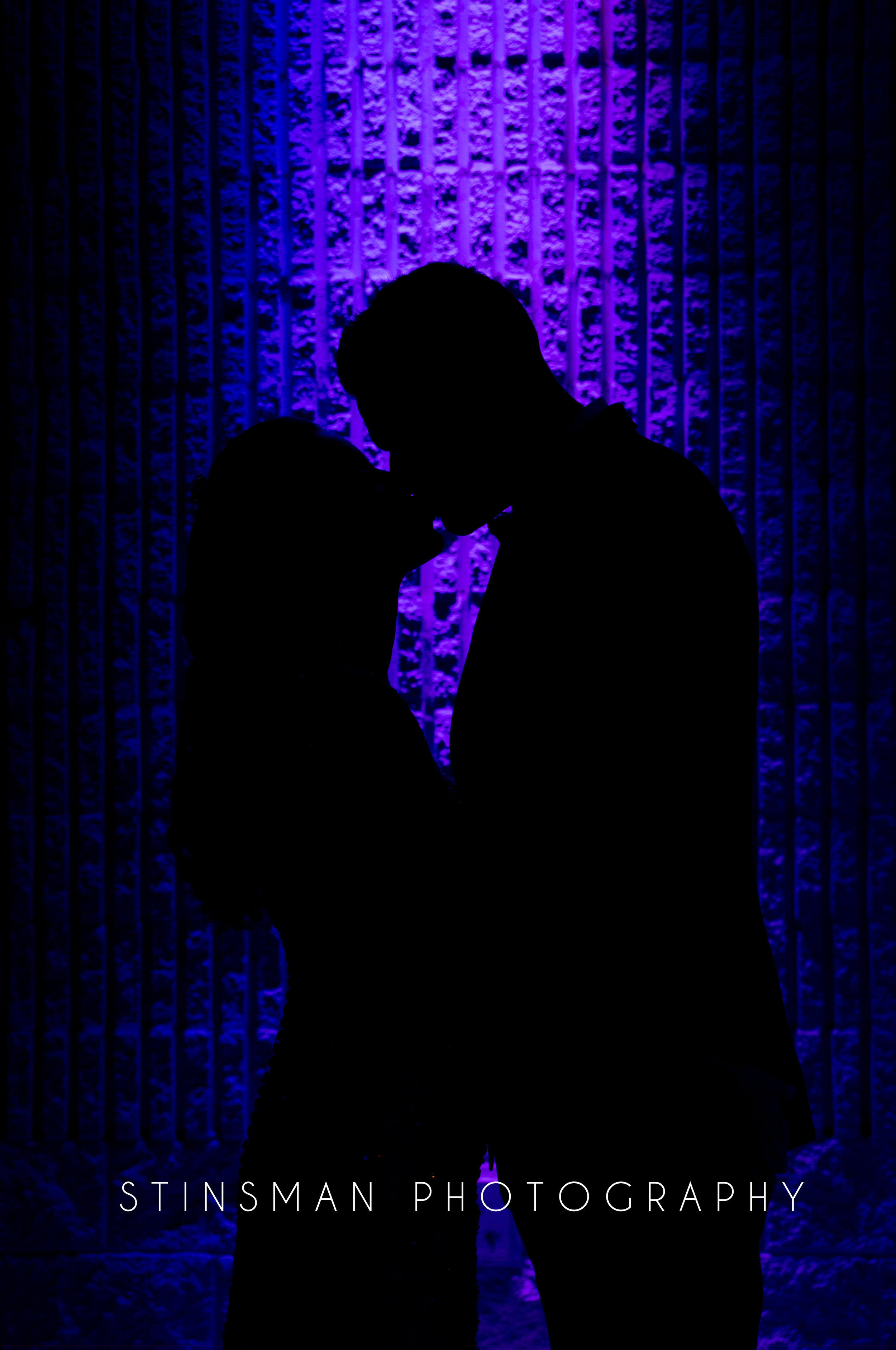 silhouette photo of the bride and groom with a purple backdrop