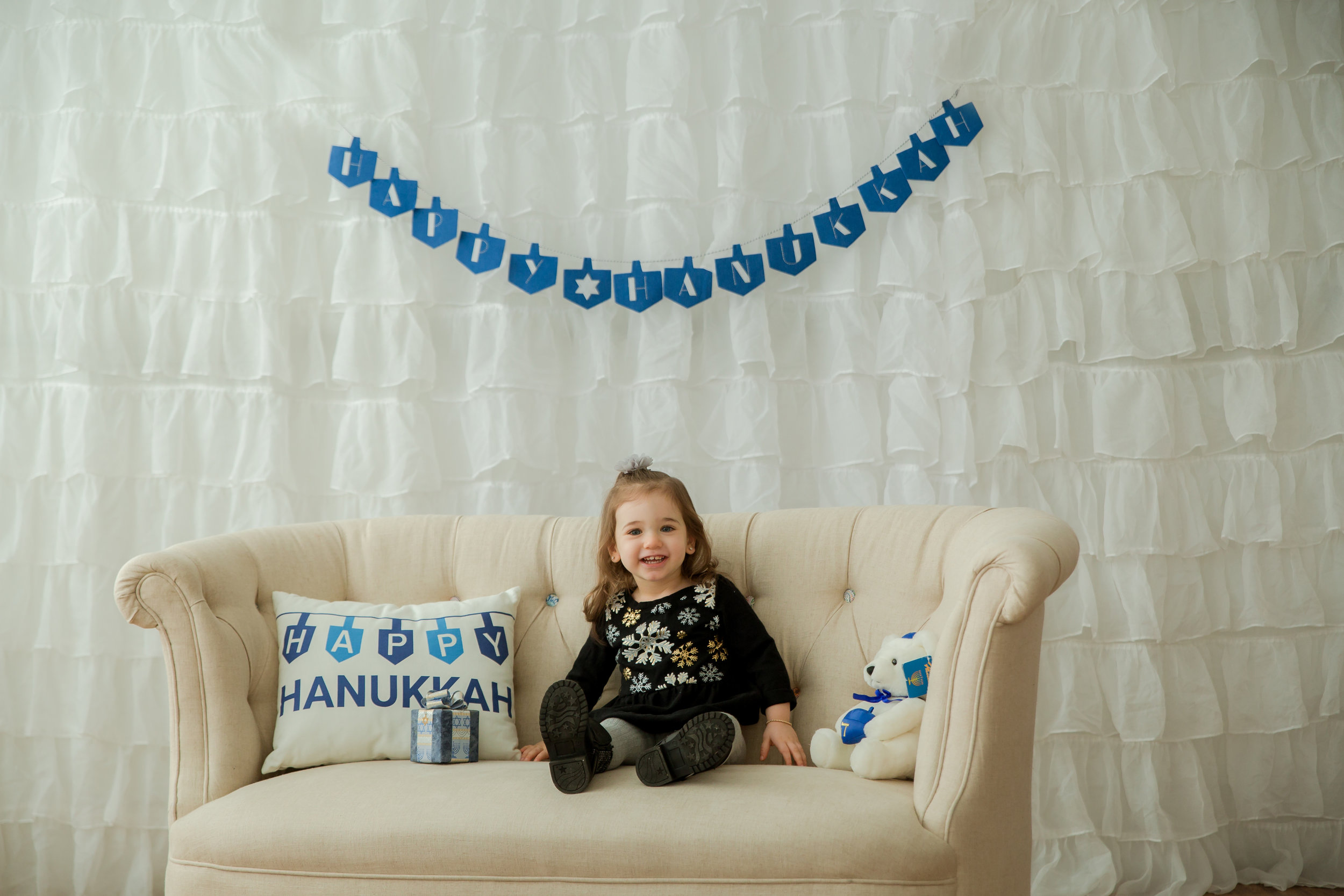 little girl wearing a black shirt with snowflakes smiling