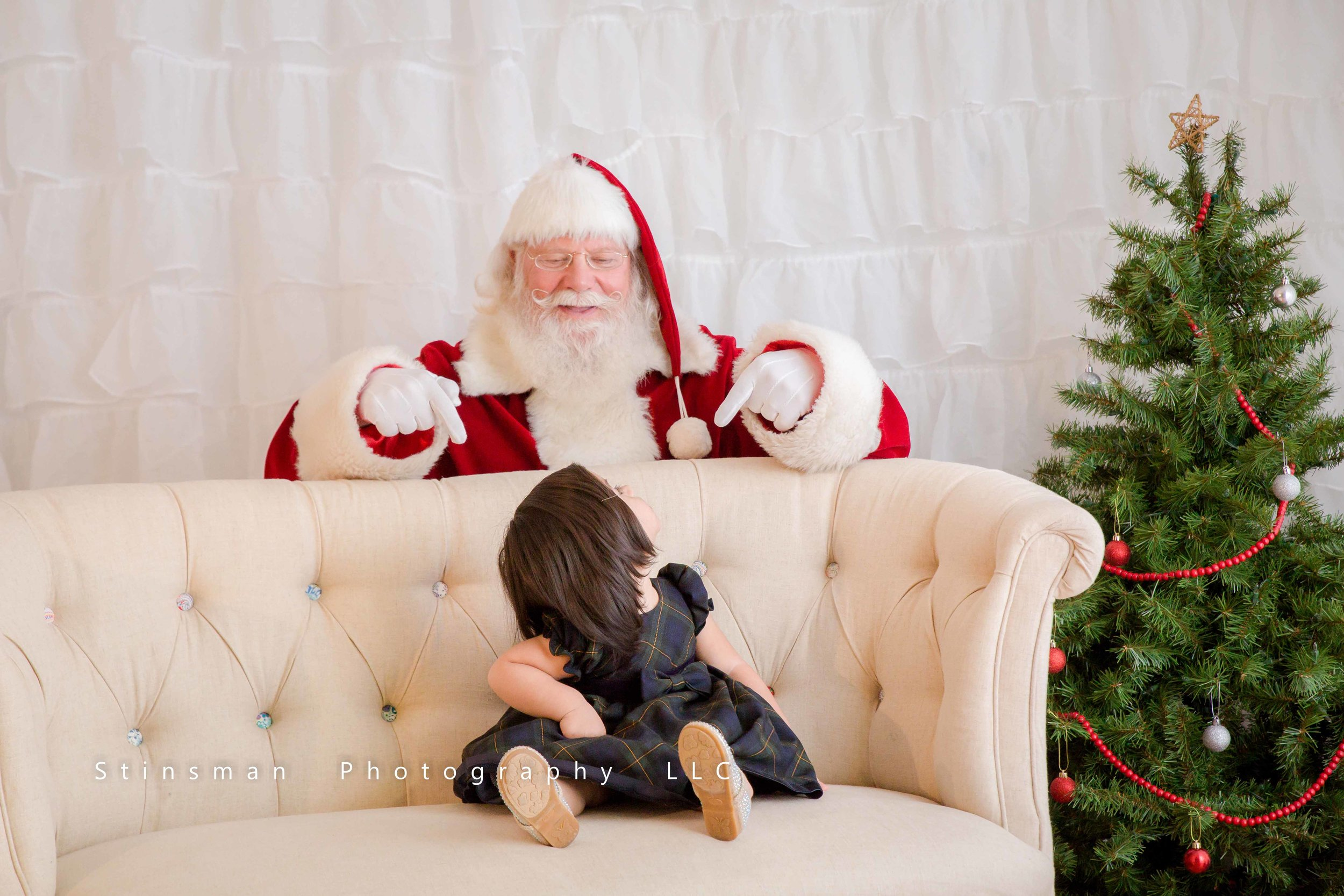 little girl sitting on a couch and Santa behind her
