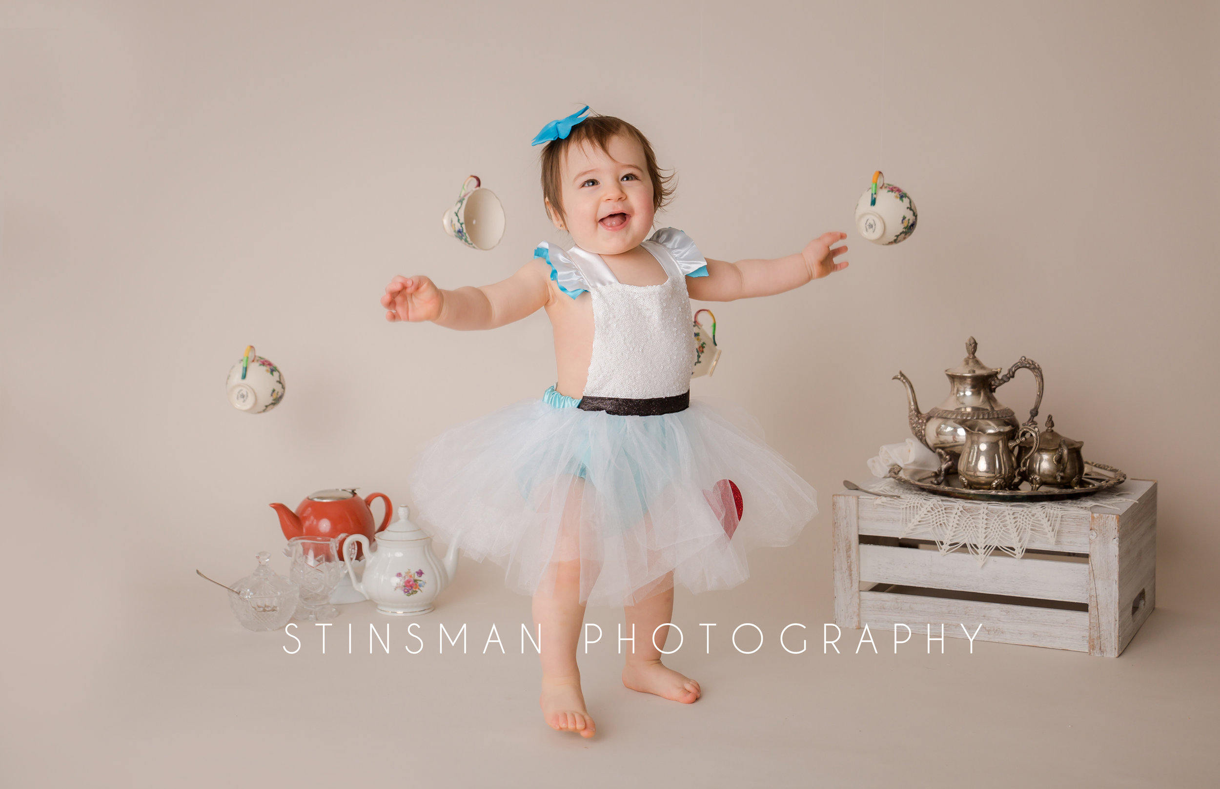 little girl smiling and going to hug the photographer in a tutu