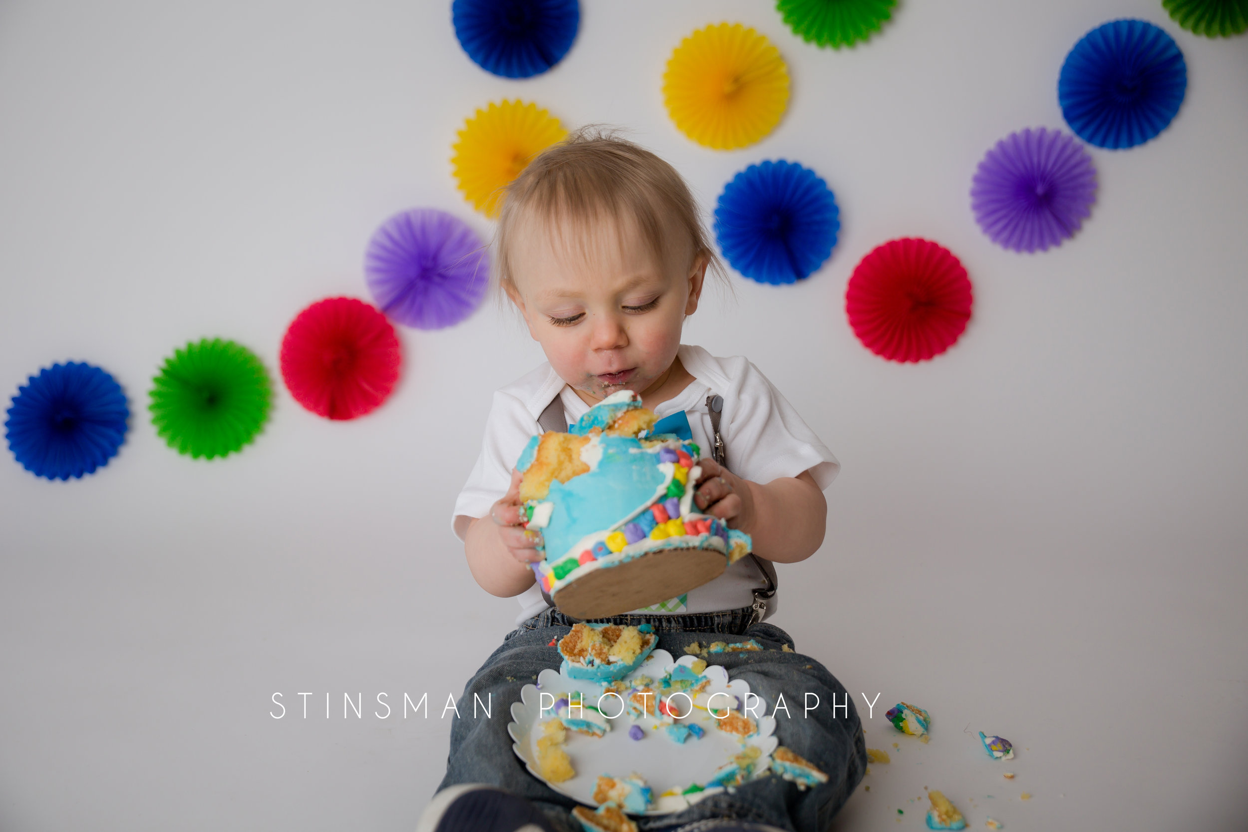 one year old boy eating cake with an inside out theme