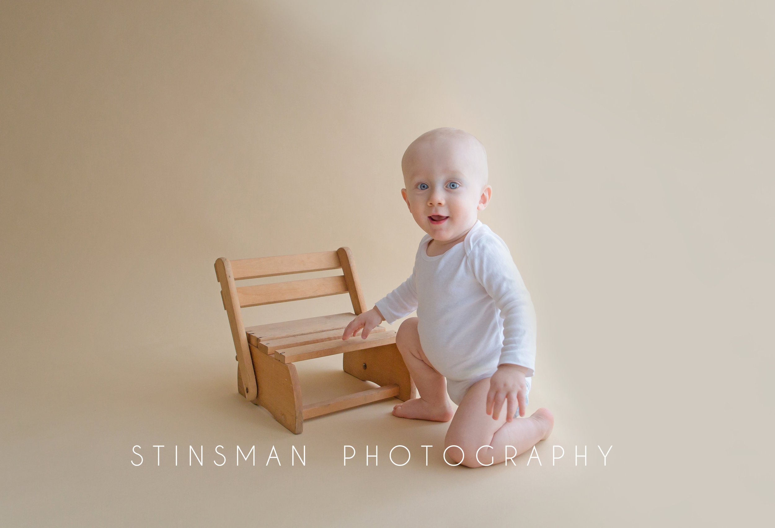 little boy sitting with a chair smiling