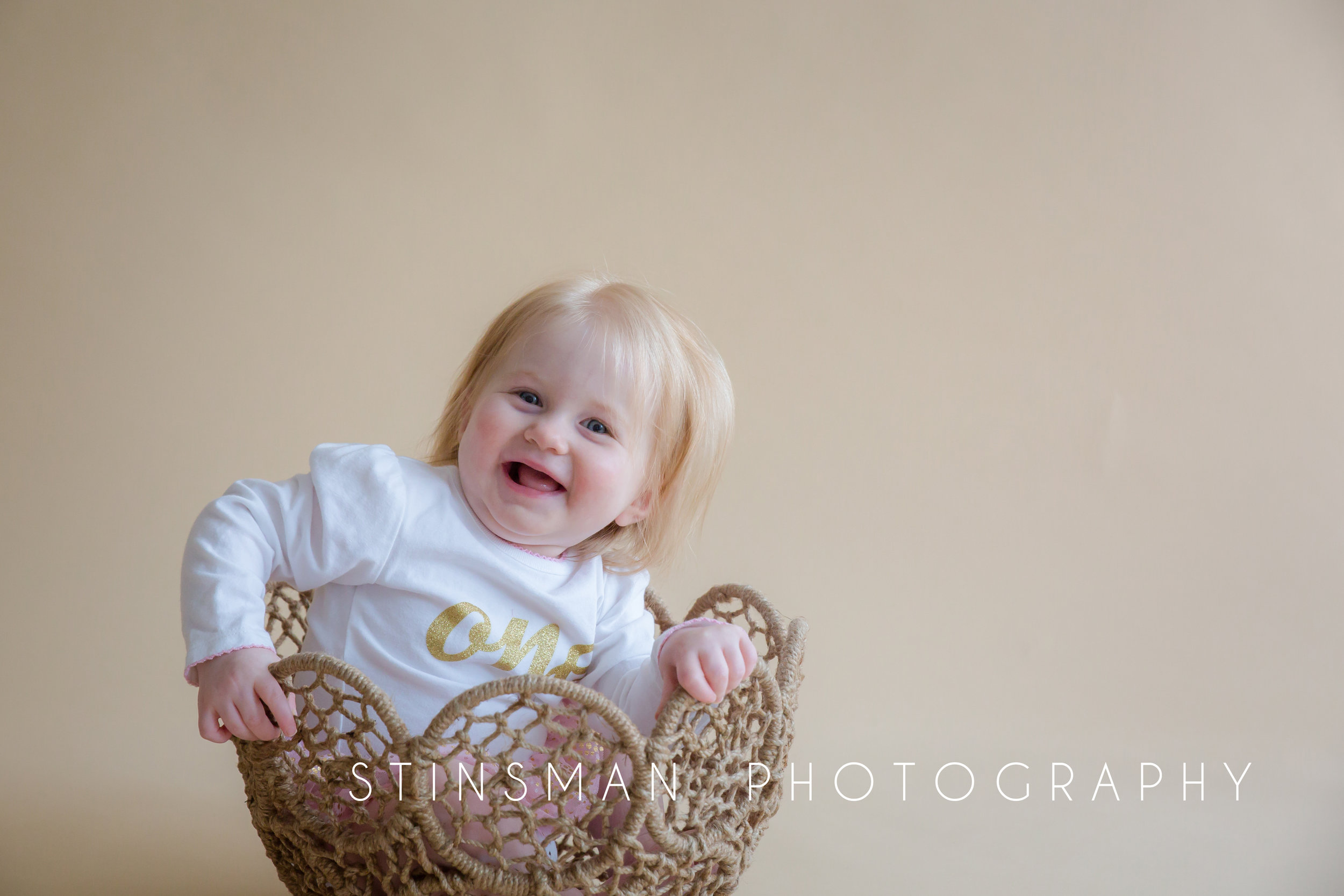 one year old girl wearing a one onesie and sitting in a bucket with her blonde long hair