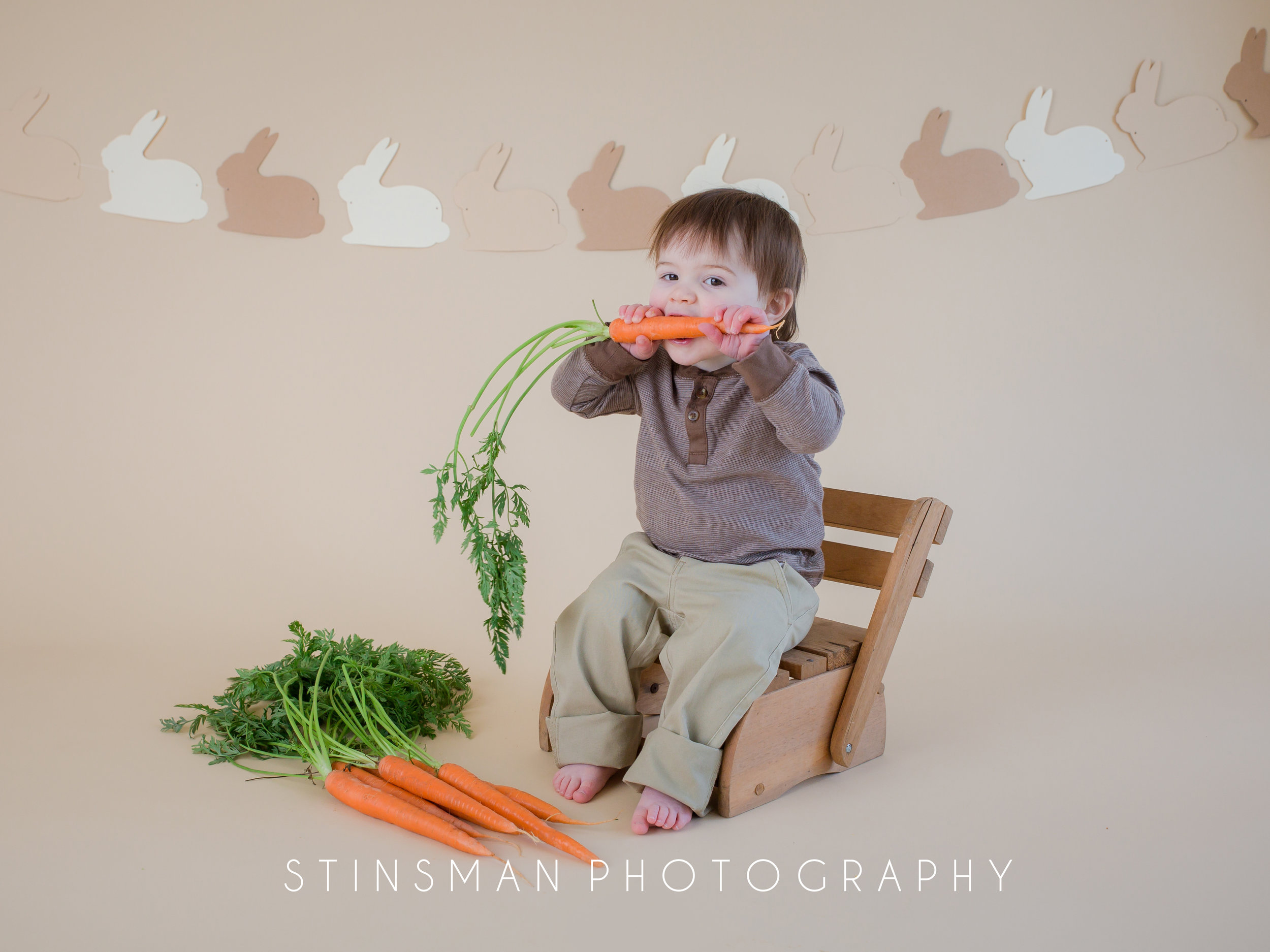 baby with brown hair eating a carrot