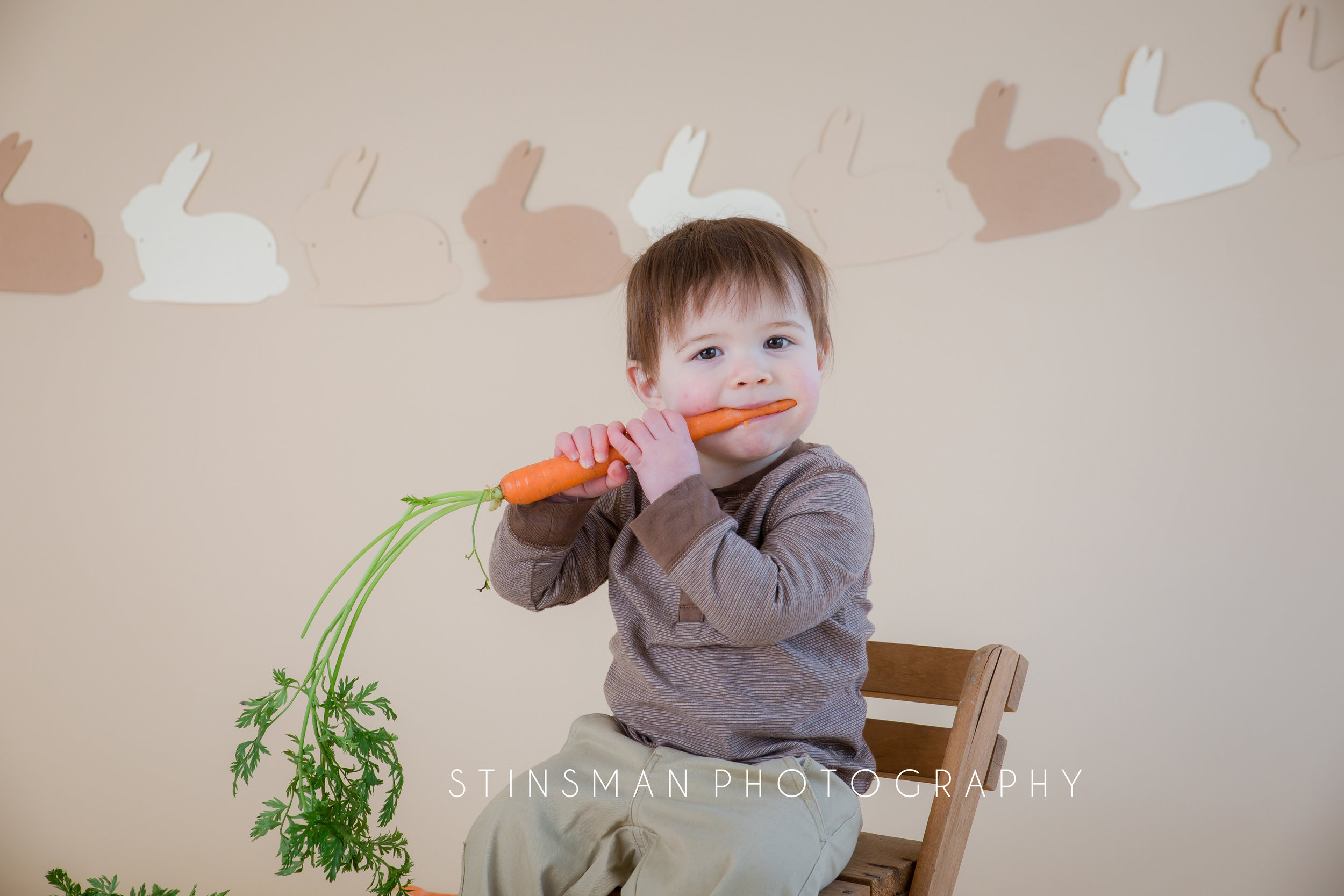 baby with two teeth sitting on a brown chair eating a carrot