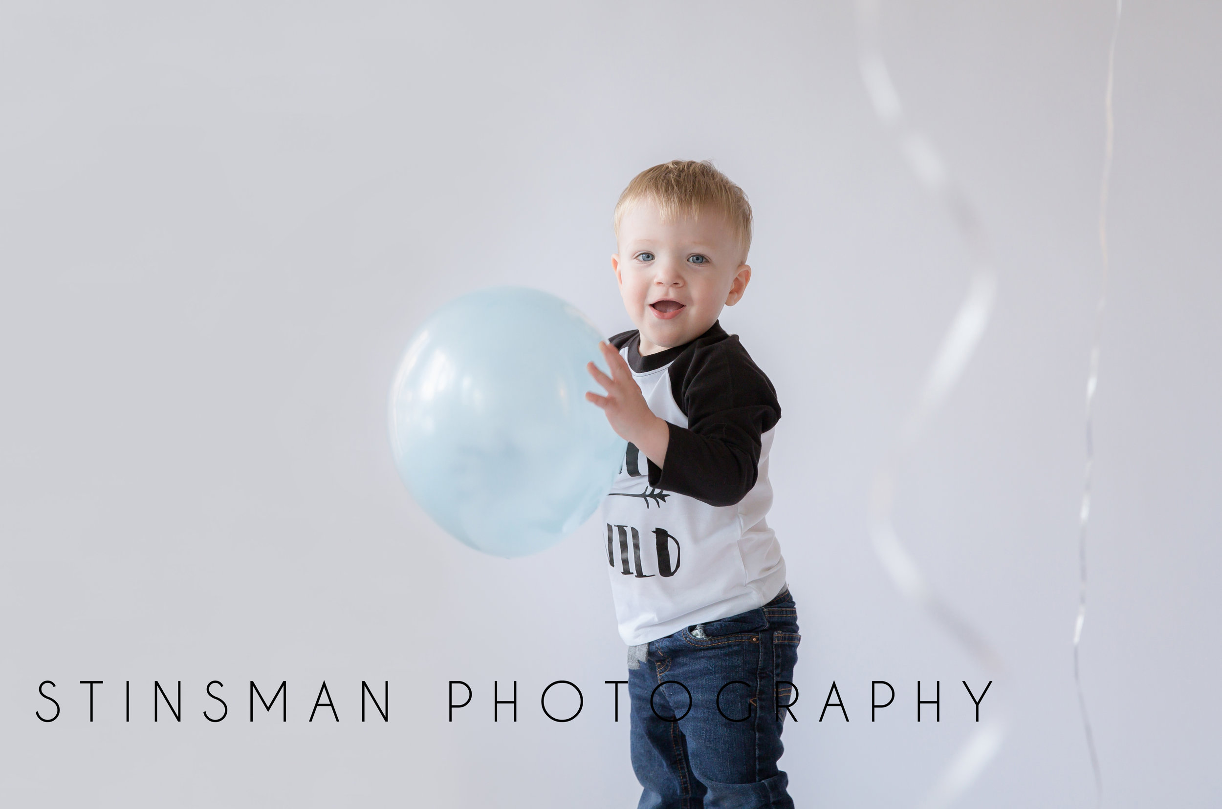two year old boy holding a light blue balloon